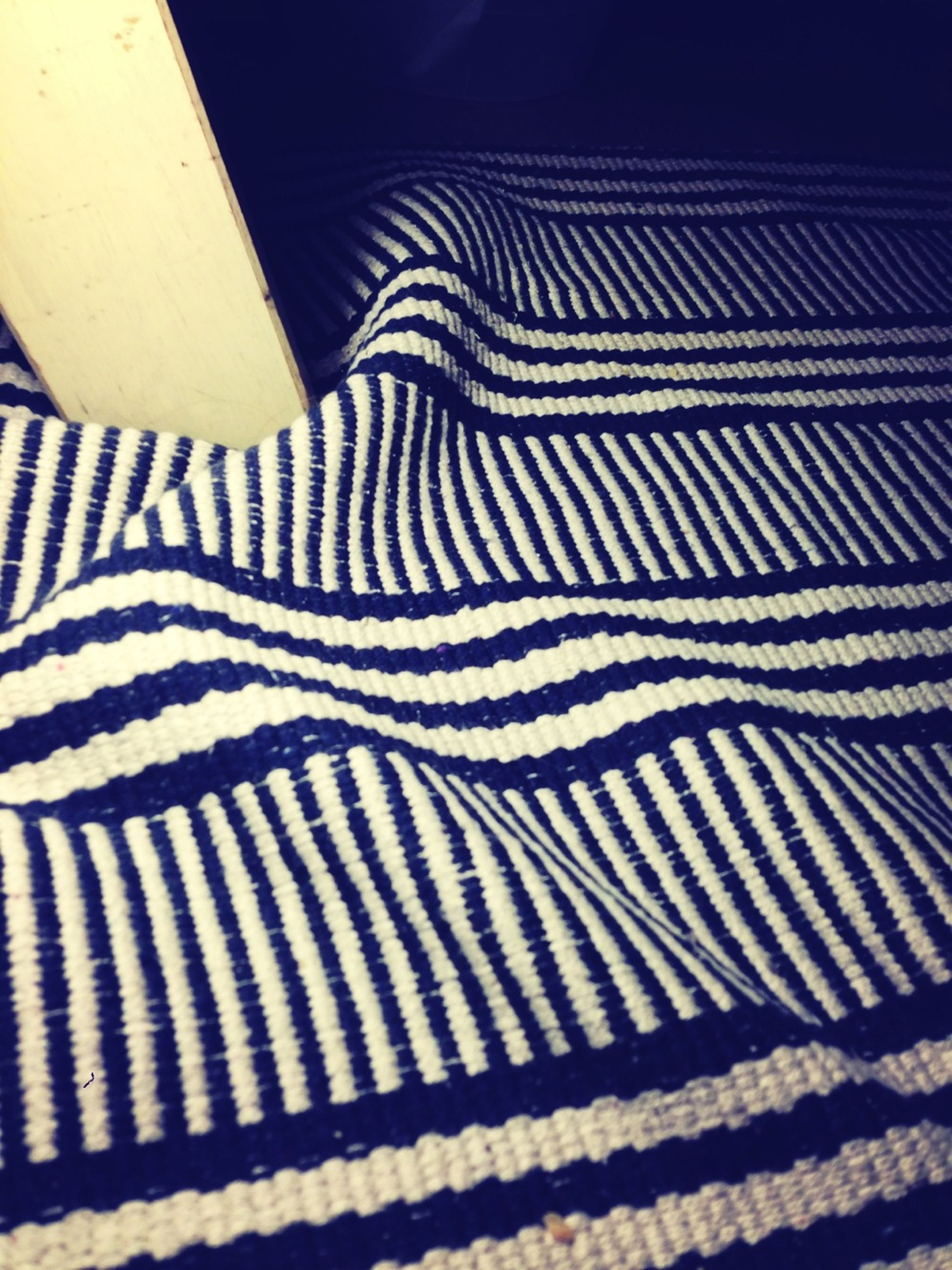 striped, pattern, indoors, animal themes, high angle view, one animal, zebra, no people, blue, close-up, design, white color, day, sunlight, fabric, textile, part of, relaxation, shadow
