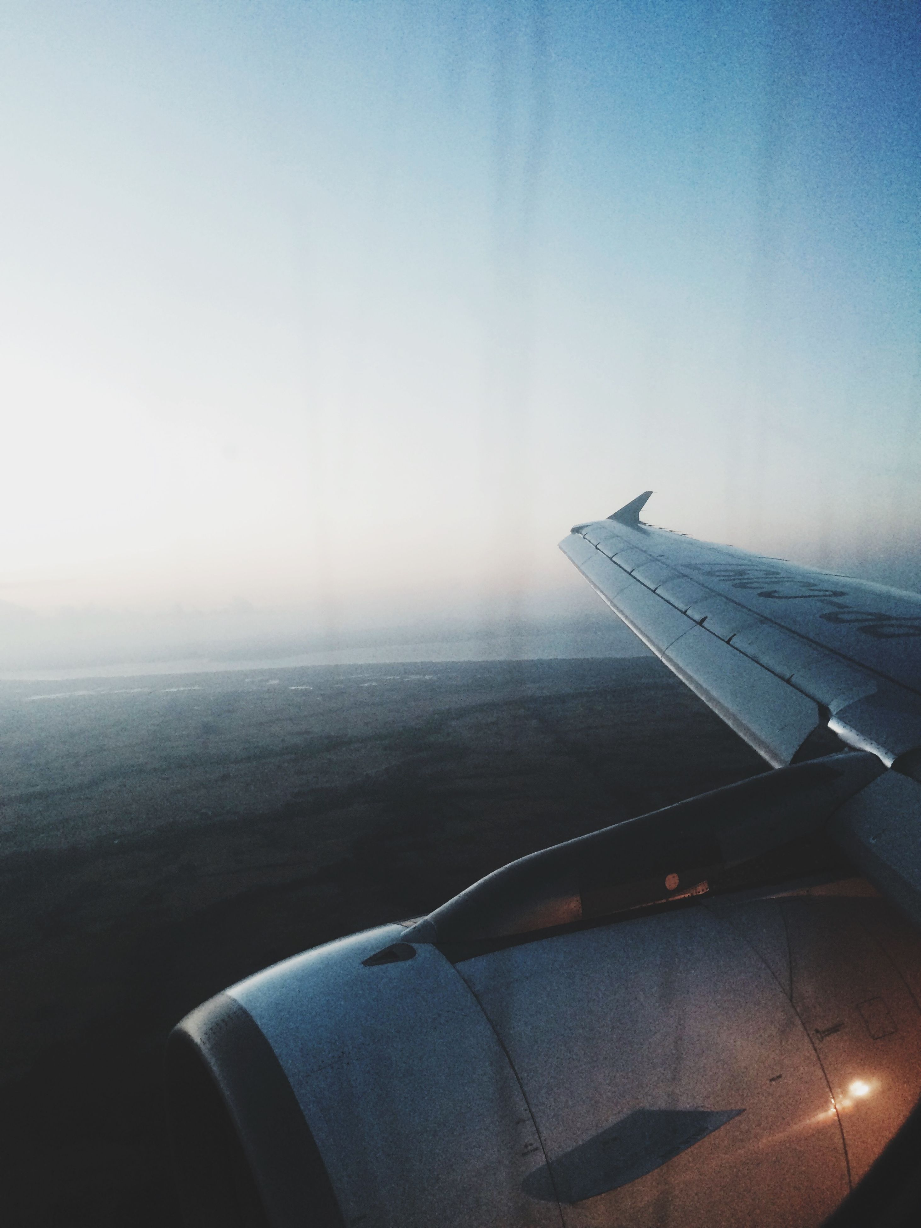 airplane, air vehicle, aircraft wing, transportation, mode of transport, flying, part of, cropped, aerial view, travel, sky, journey, mid-air, on the move, sea, aeroplane, scenics, airplane wing, public transportation, clear sky
