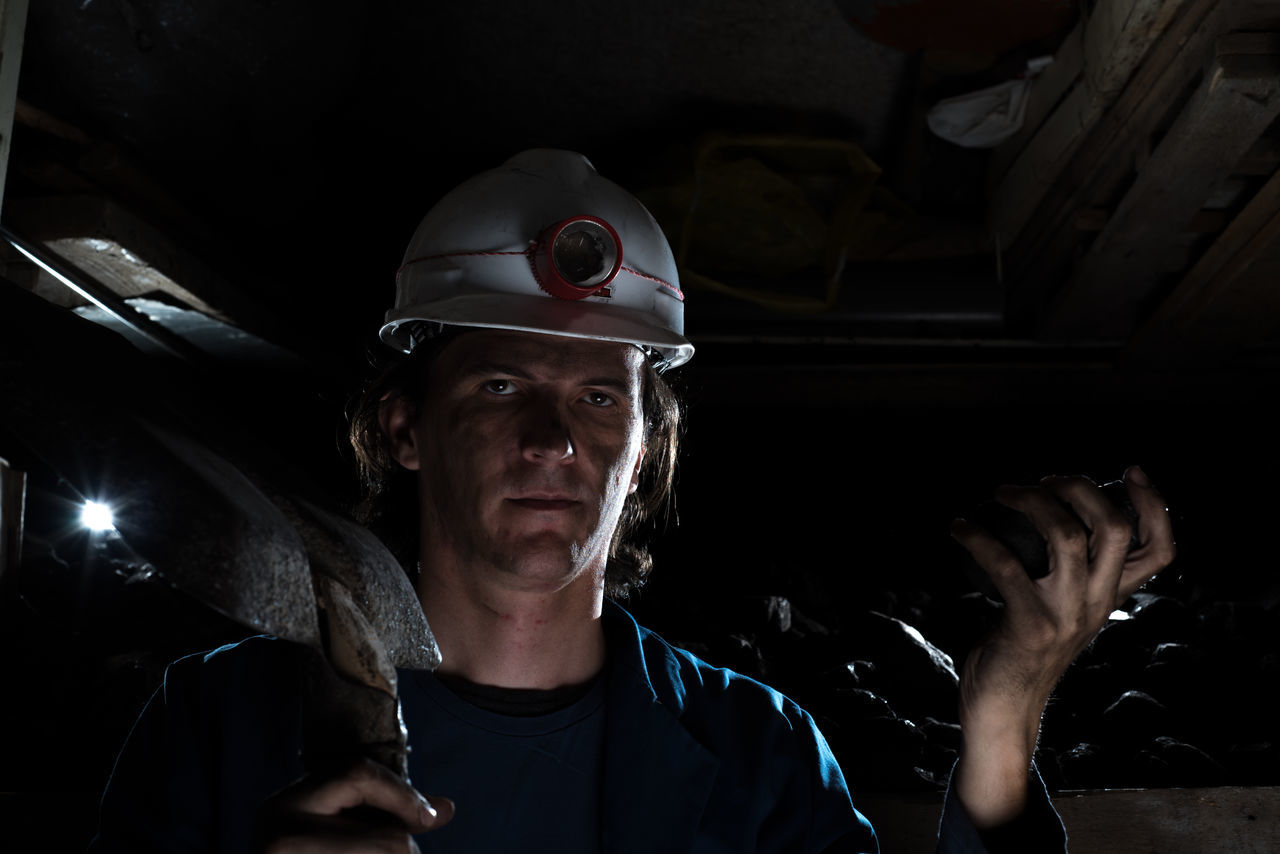 miner holding coal and shovel in hands Close-up Coal Coalmine Gold Hard Headshot Headwear Indastrial Indoors  Industry Mine Miner Minerals Mining Mining Industry One Person Ore People Protective Workwear Shovel Work