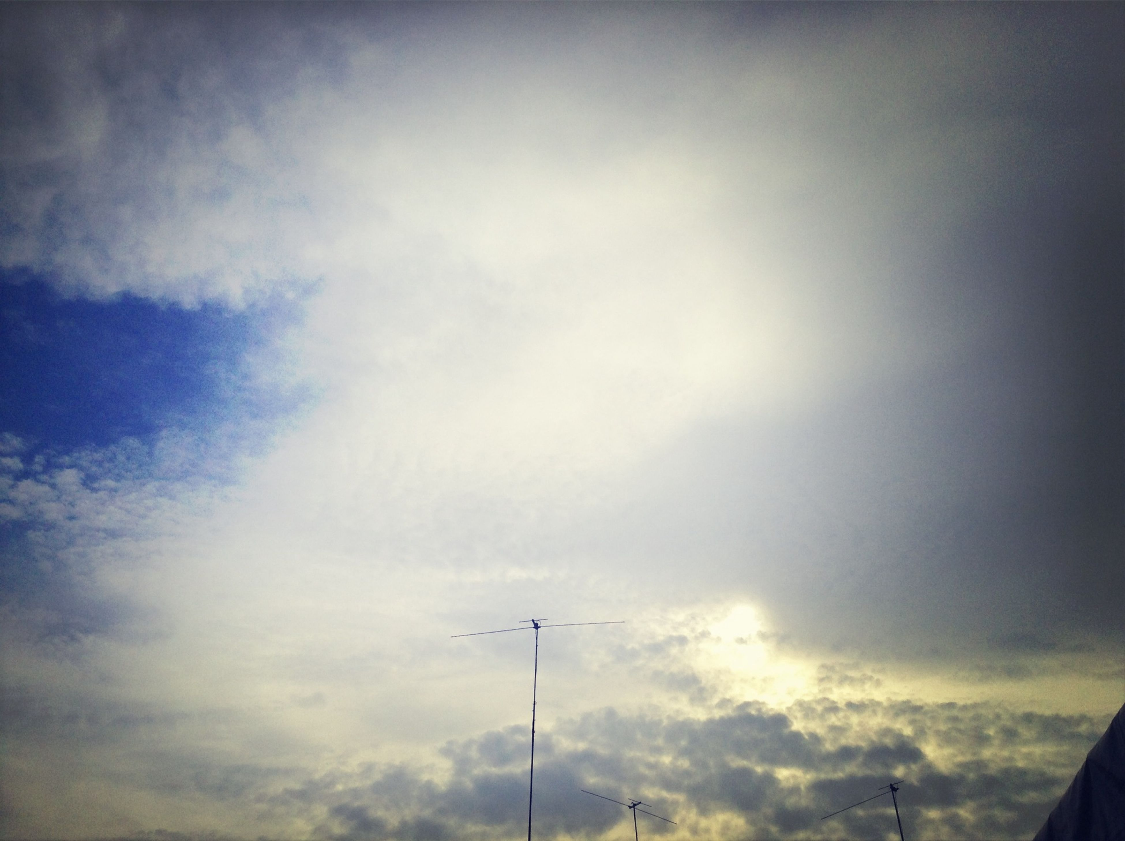 low angle view, sky, cloud - sky, cloudy, silhouette, cloud, street light, outdoors, nature, high section, day, no people, tranquility, beauty in nature, overcast, scenics, lighting equipment, built structure, airplane, dusk
