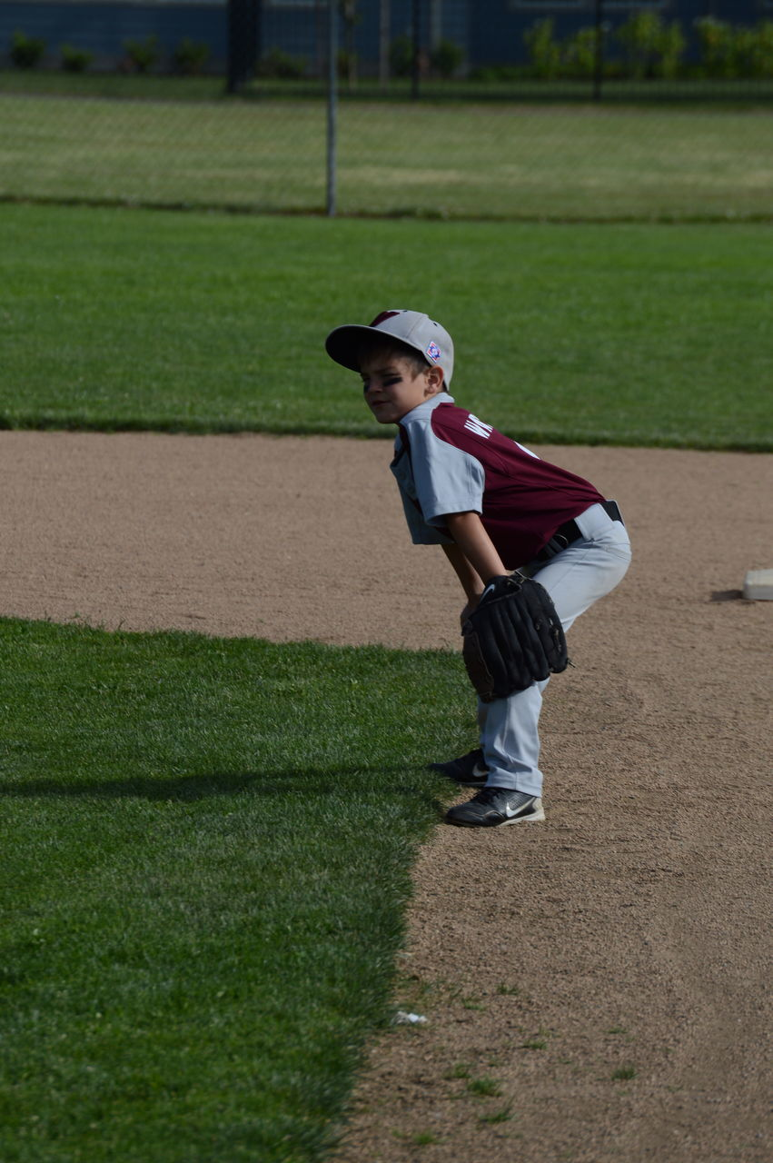 childhood, boys, one person, grass, full length, casual clothing, leisure activity, real people, elementary age, day, green color, lifestyles, baseball - sport, outdoors, one boy only, standing, baseball helmet, people