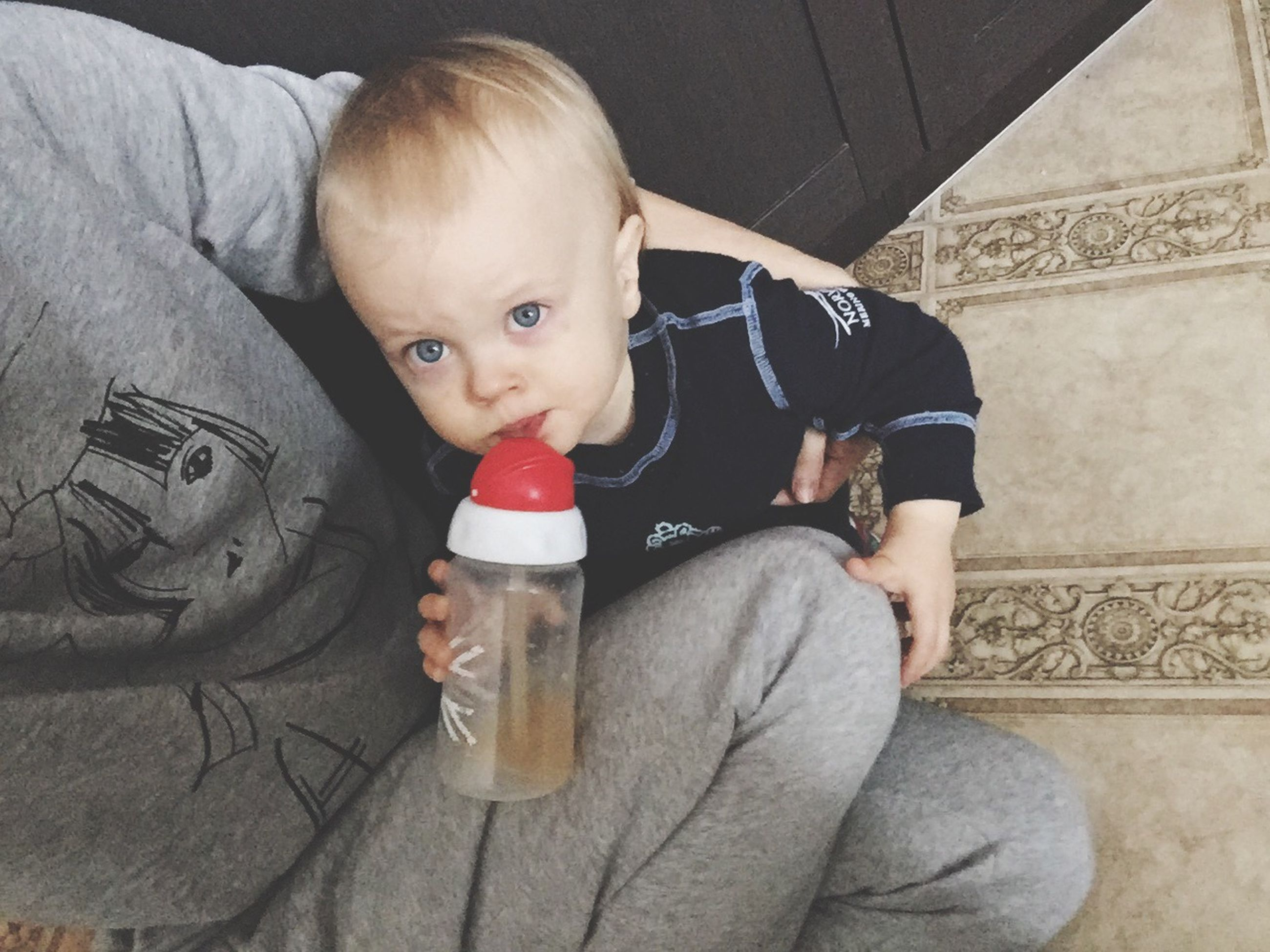 baby, babyhood, innocence, drinking, casual clothing, holding, toddler, sucking, looking at camera, indoors, portrait, childhood, full length, real people, food and drink, people, one person, babies only, eating, human body part, domestic life, adult, day