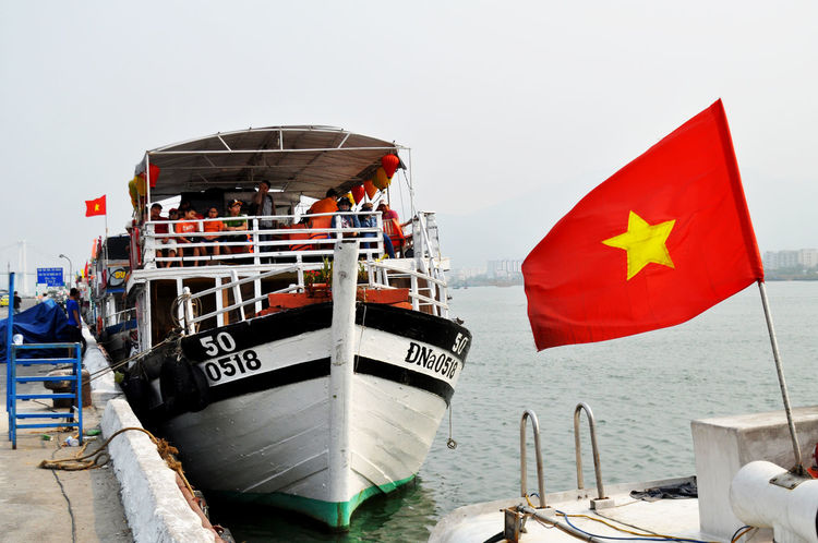 Tour boat ready to leave wharf on Han River in Da Nang, Vietnam. All Aboard Boats Da Nang Day Excursions Flags Han River Lifejackets Lifestyle National Flags Outdoors Ready To Go Red Rivers Sightseeing Tourism Tourists Travel Vietnam Waiting Water Wharf Yellow Star