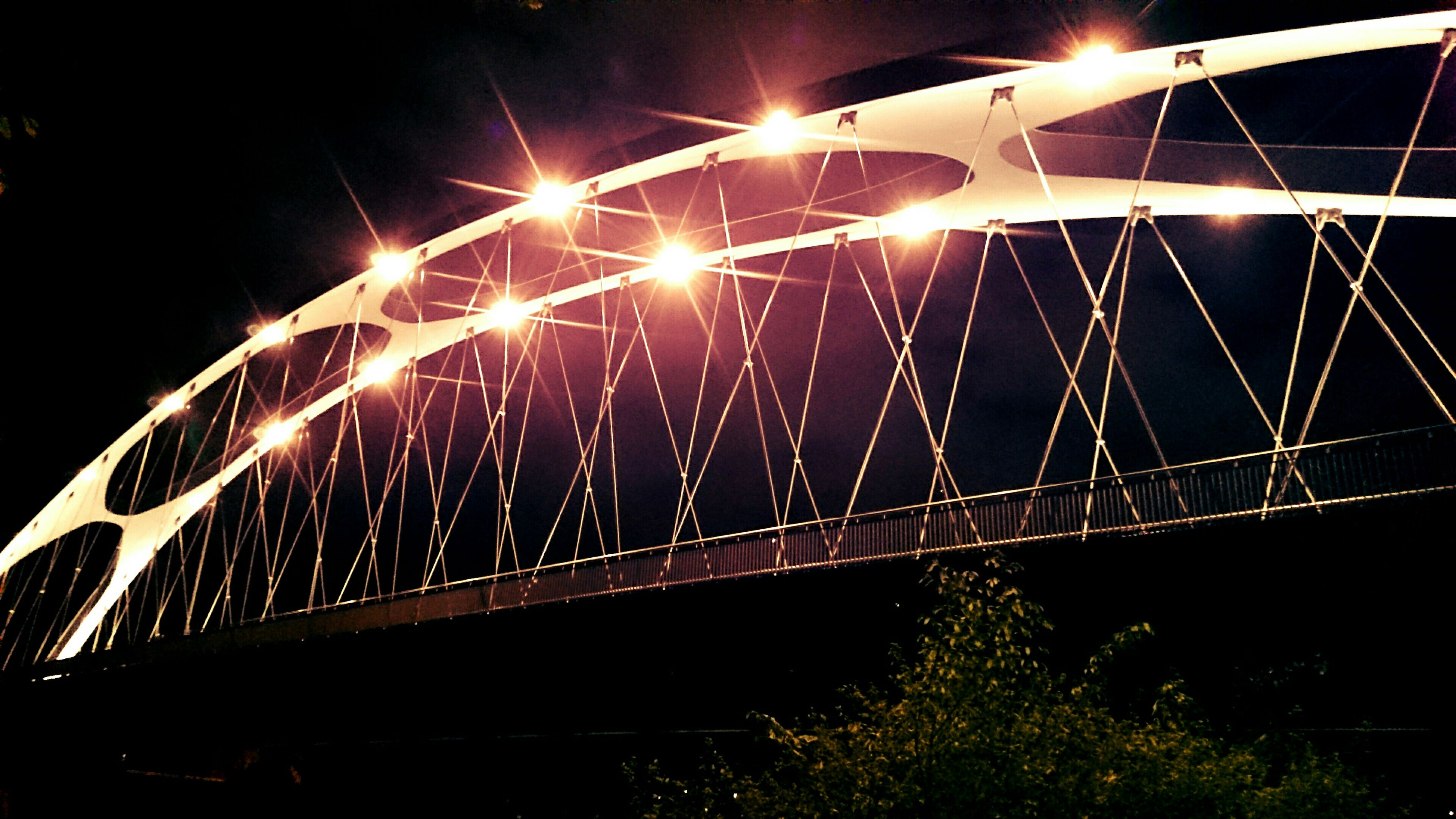 night, illuminated, bridge - man made structure, connection, built structure, architecture, transportation, engineering, low angle view, bridge, arch, street light, city, outdoors, sky, no people, railing, lighting equipment, light trail, reflection