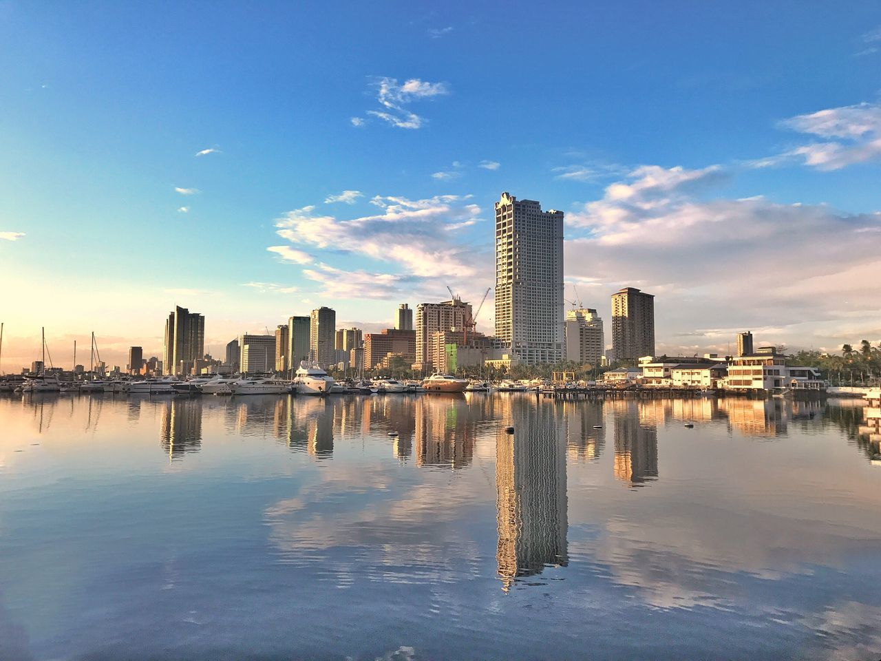 skyscraper, water, architecture, building exterior, sky, city, built structure, reflection, cityscape, urban skyline, modern, waterfront, outdoors, no people, nature, day