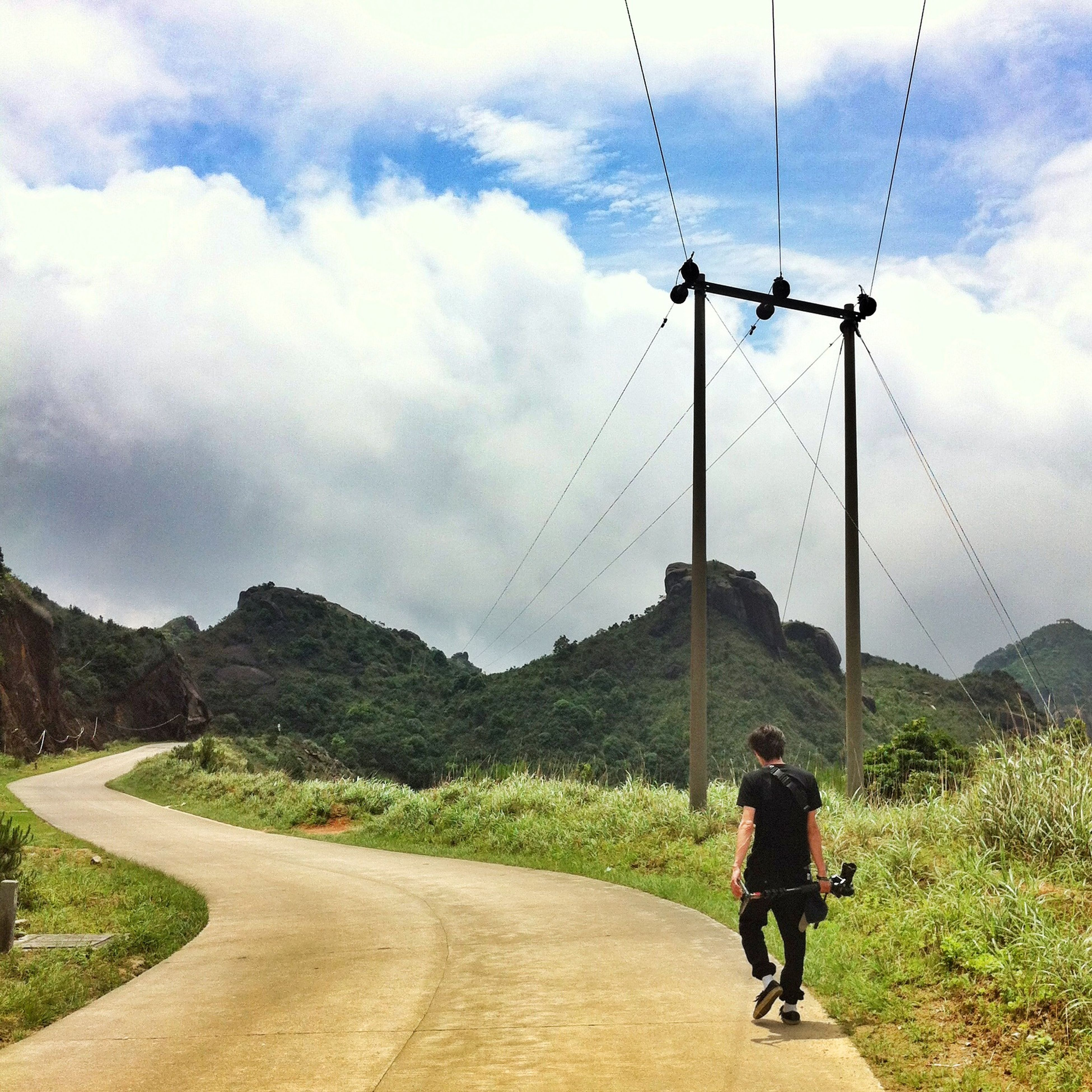 full length, sky, lifestyles, leisure activity, rear view, men, cloud - sky, landscape, mountain, casual clothing, transportation, road, walking, the way forward, cloud, standing, nature, person