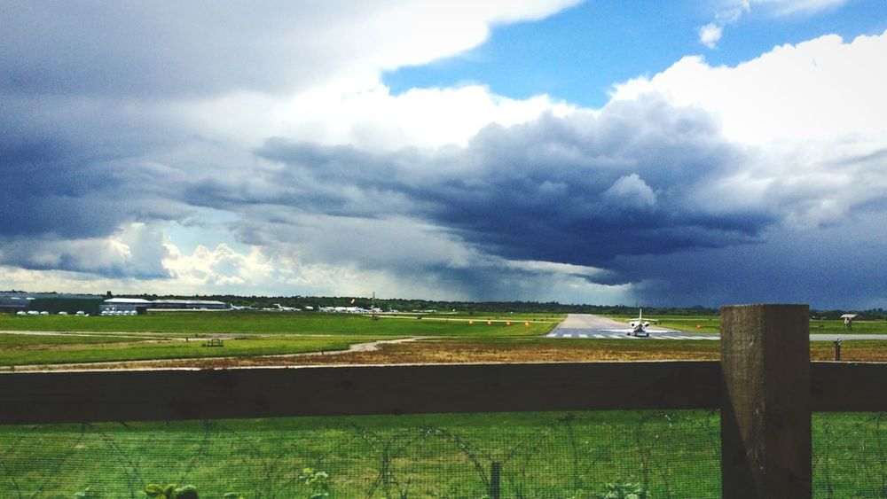 Bad weather small plane waits on runway. Cloud and sun.
