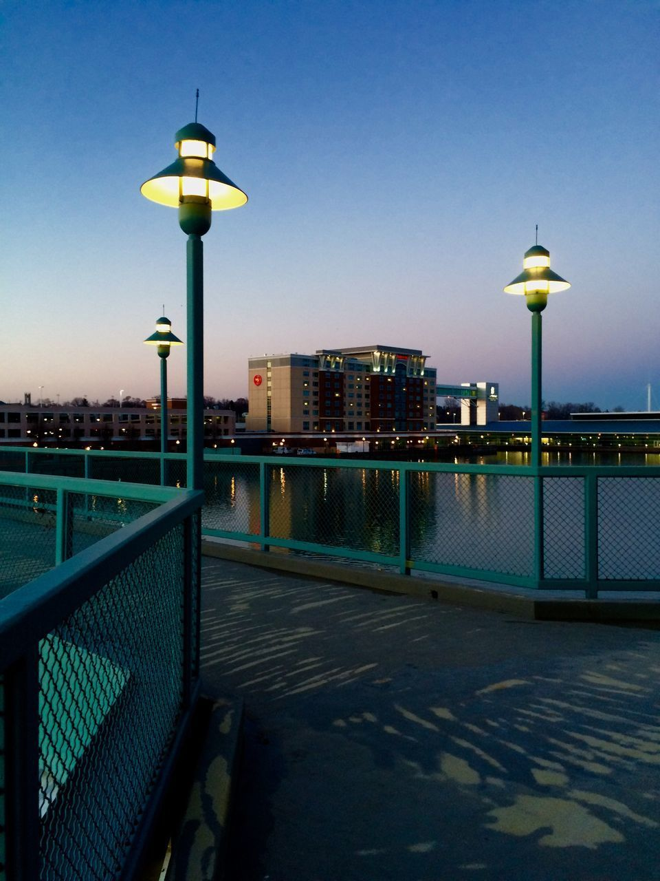 illuminated, lighting equipment, street light, architecture, built structure, city, water, building exterior, blue, river, clear sky, sky, outdoors, waterfront, no people, cityscape, night, urban skyline, nature
