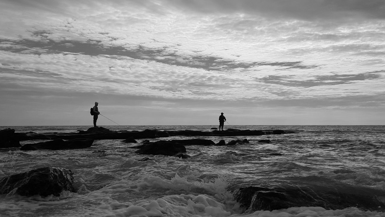 People Standing On Rock At Seaside Against Cloudy Sky