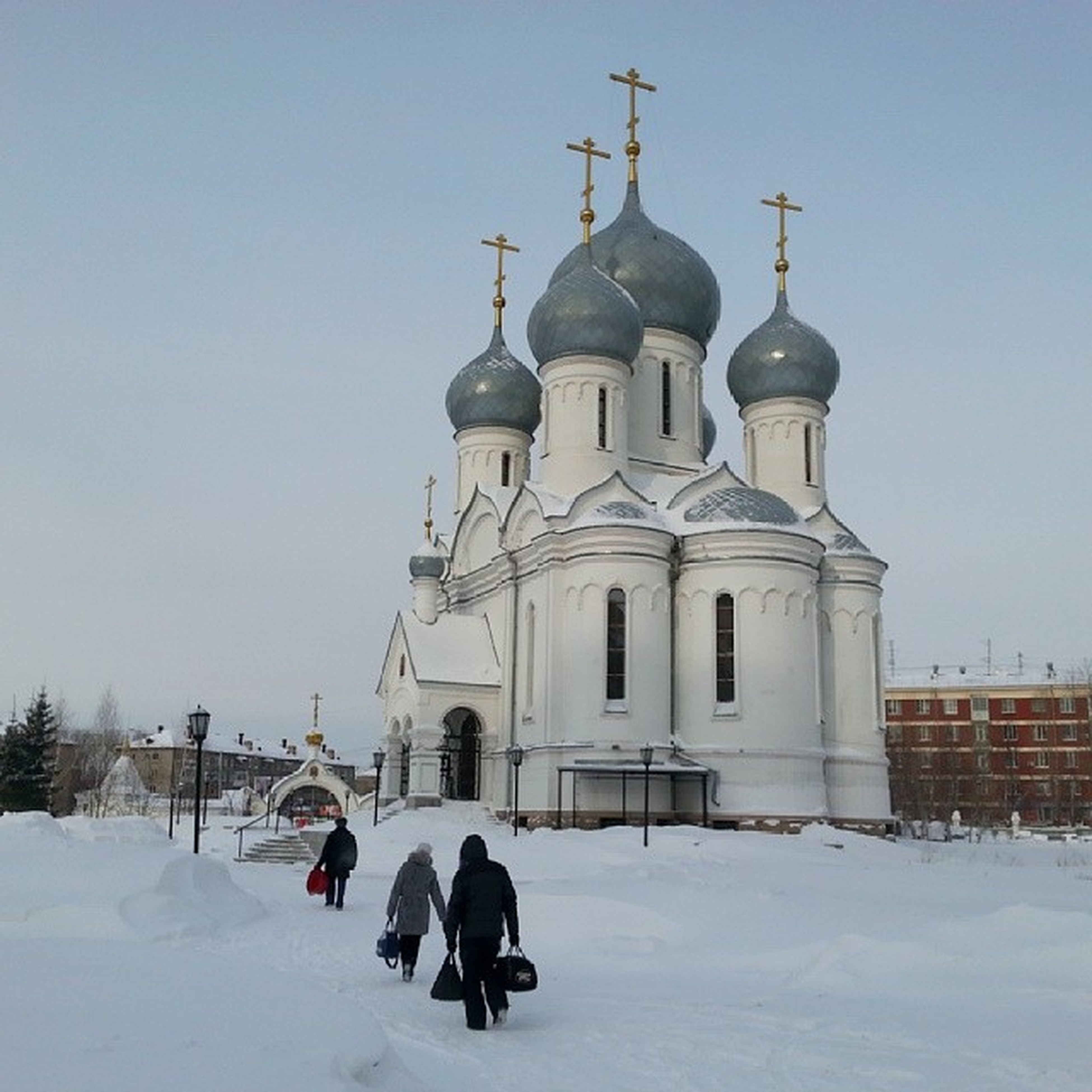 winter, snow, cold temperature, architecture, built structure, building exterior, clear sky, season, place of worship, church, religion, rear view, men, walking, spirituality, dome, lifestyles