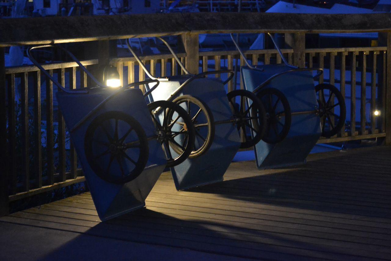 Wheelbarrows Leaning On Footbridge Railing At Night
