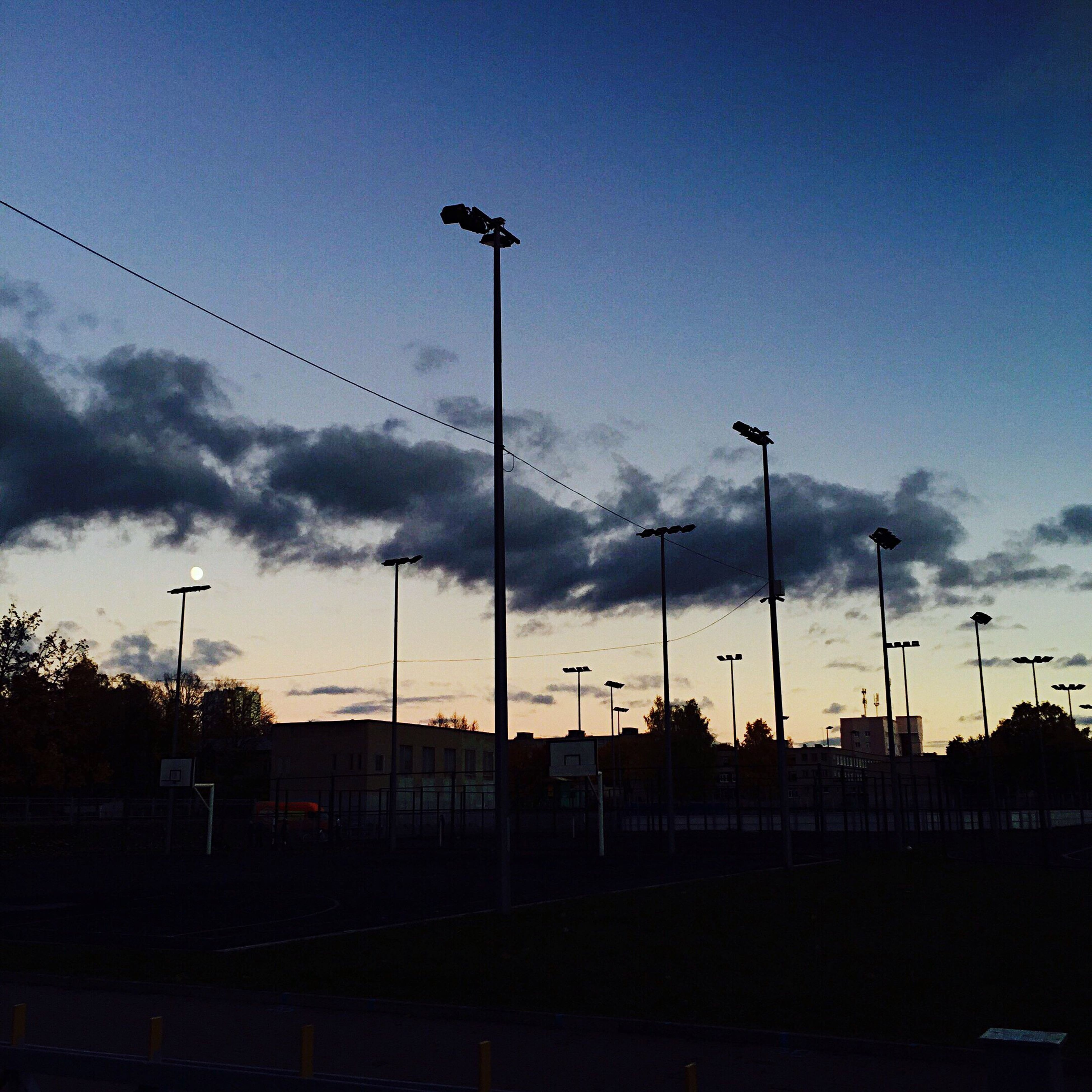 building exterior, built structure, sky, architecture, silhouette, street light, low angle view, cloud - sky, dusk, electricity pylon, city, electricity, cloud, power line, lighting equipment, fuel and power generation, house, outdoors, no people, sunset