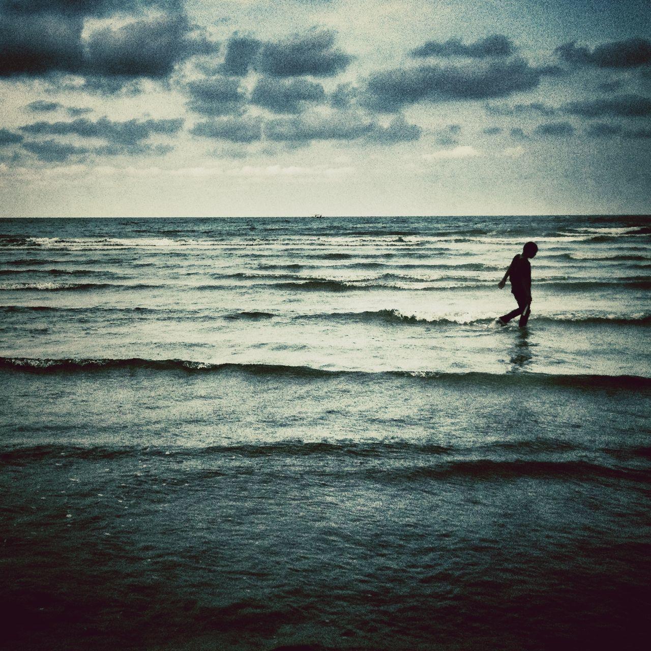 Silhouette Man Walking In Calm Sea