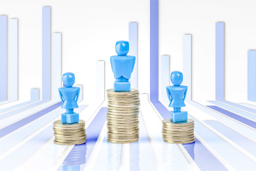 One male and two female figurines standing on piles of coins and bar graph. Income inequality concept. Bar Graph Blue Business Business Finance And Industry Close-up Coins Day Female Figurines  Gender Equality Indoors  Leisure Games Male No People Pile Of Coins Stack Strategy Wage Gap White Background