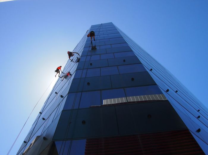 3 Men Working Abseiling Office Building Reflections Urban Workplace Window Cleaners High Angle View Working Safety