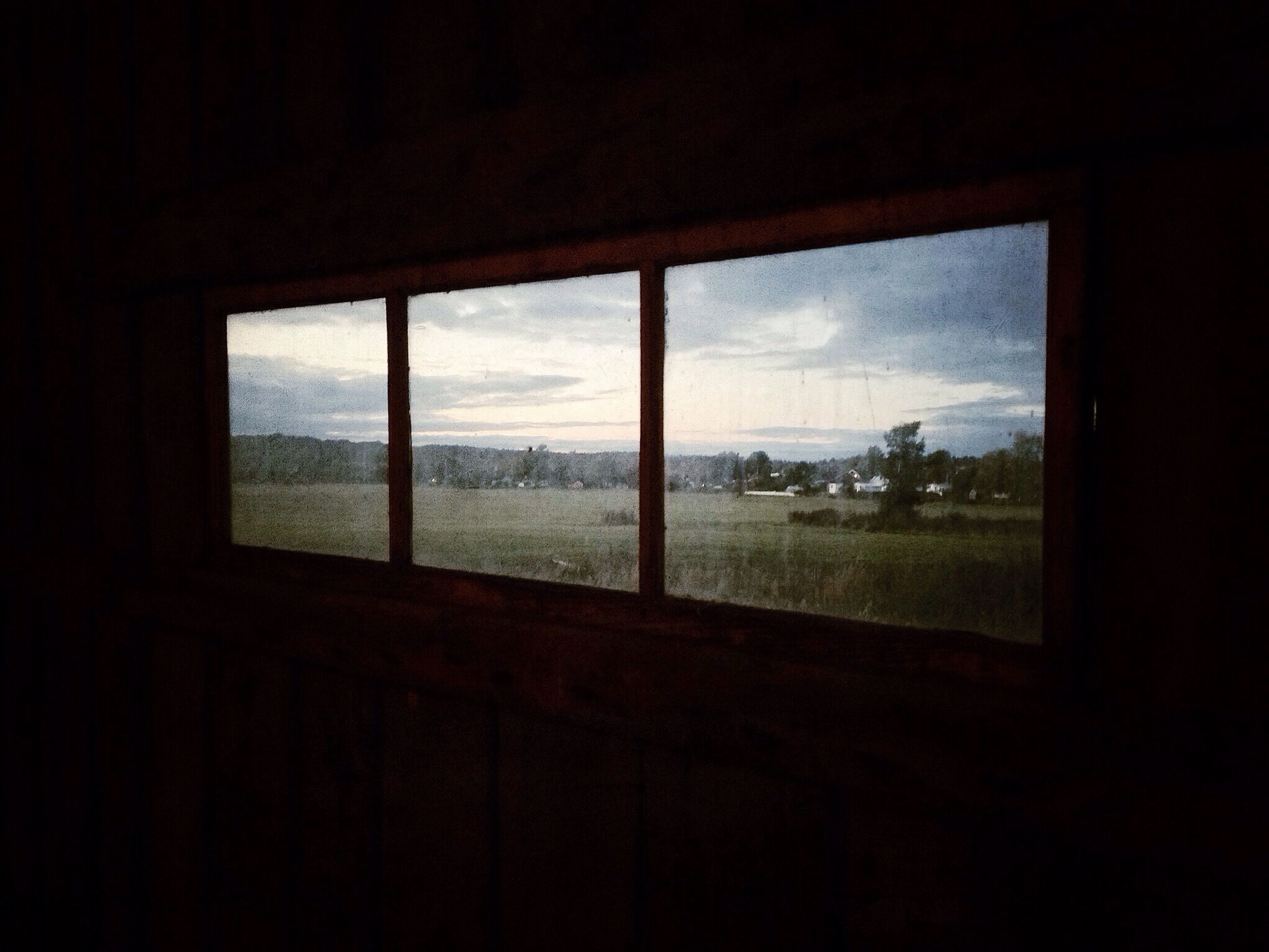 window, indoors, glass - material, transparent, sky, looking through window, built structure, architecture, tree, silhouette, glass, house, weather, cloud - sky, dark, day, nature, no people, landscape, building exterior