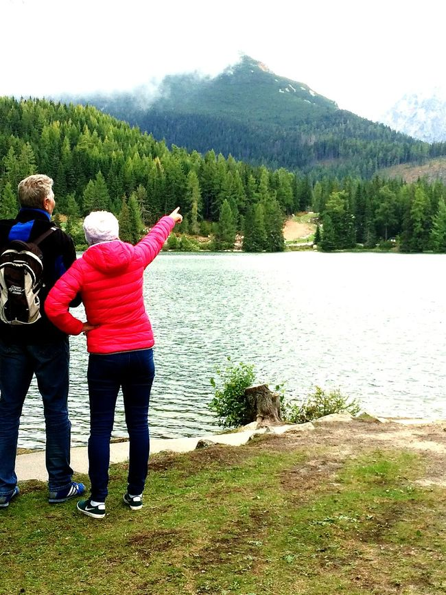 Full Length Two People Rear View Casual Clothing Water Togetherness Leisure Activity Carefree Outdoors Mature Adult Bonding Nature Day Real People Standing Happiness Tree Jumping Grass Beauty In Nature