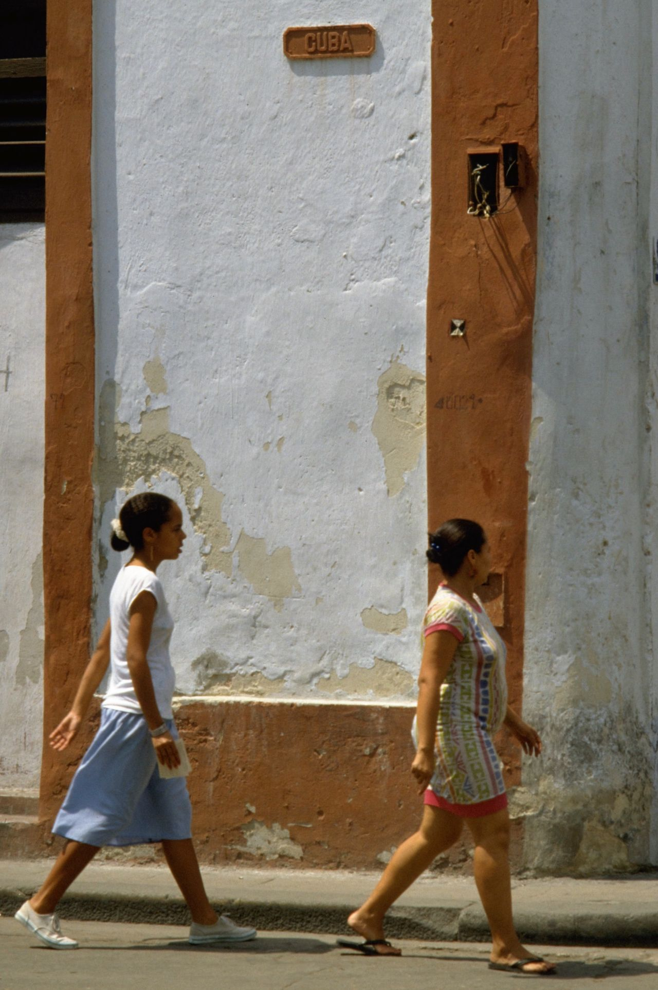 Two Cuban ladies walking down Cuba Calle in Havana, Republic of Cuba. Cuba is the largest island in the Caribbean, and the second-most populous after Hispaniola (Dominican Republic and Haiti). Havana features some wonderful Spanish colonial architecture within its 16th-century core, Old Havana. Paint may be peeling off the walls and street lights don't always work but there are plenty of photo opportunities for street photographers with an eye for the candid shot. http://pics.travelnotes.org Calle Candid Caribbean Casual Cuba Cuban Cubano Havana Islands In The Caribbean Latin America Latinos Michel Guntern Old Town Plain People And Places Simplicity Street Life Street Photography Travel Travel Photography Travel Photos Travel Pics Up Close Street Photography Women Snap A Stranger