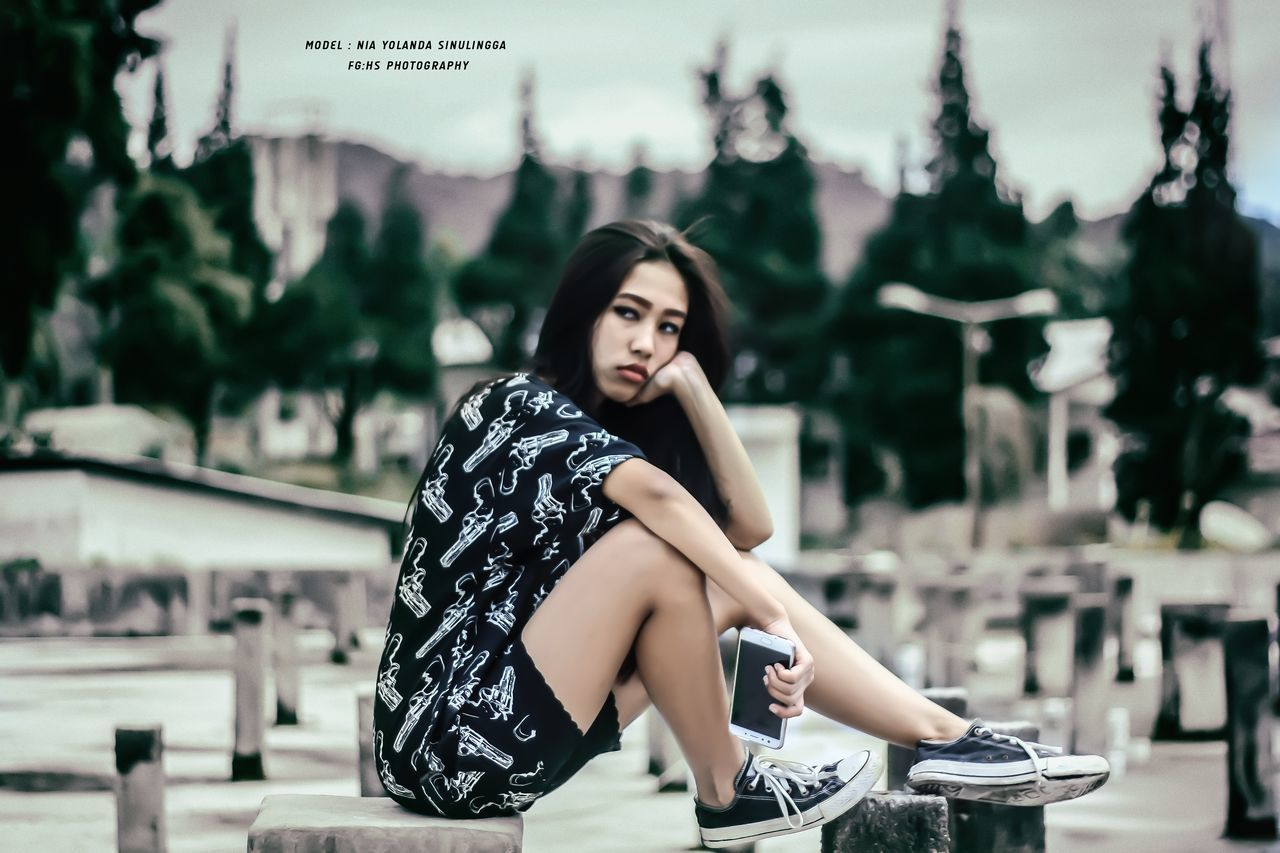 focus on foreground, beautiful woman, sitting, one person, young adult, fashion, outdoors, young women, real people, beauty, full length, lifestyles, leisure activity, day, relaxation, portrait, looking at camera, legs crossed at knee, fashion model, tree, one young woman only, people