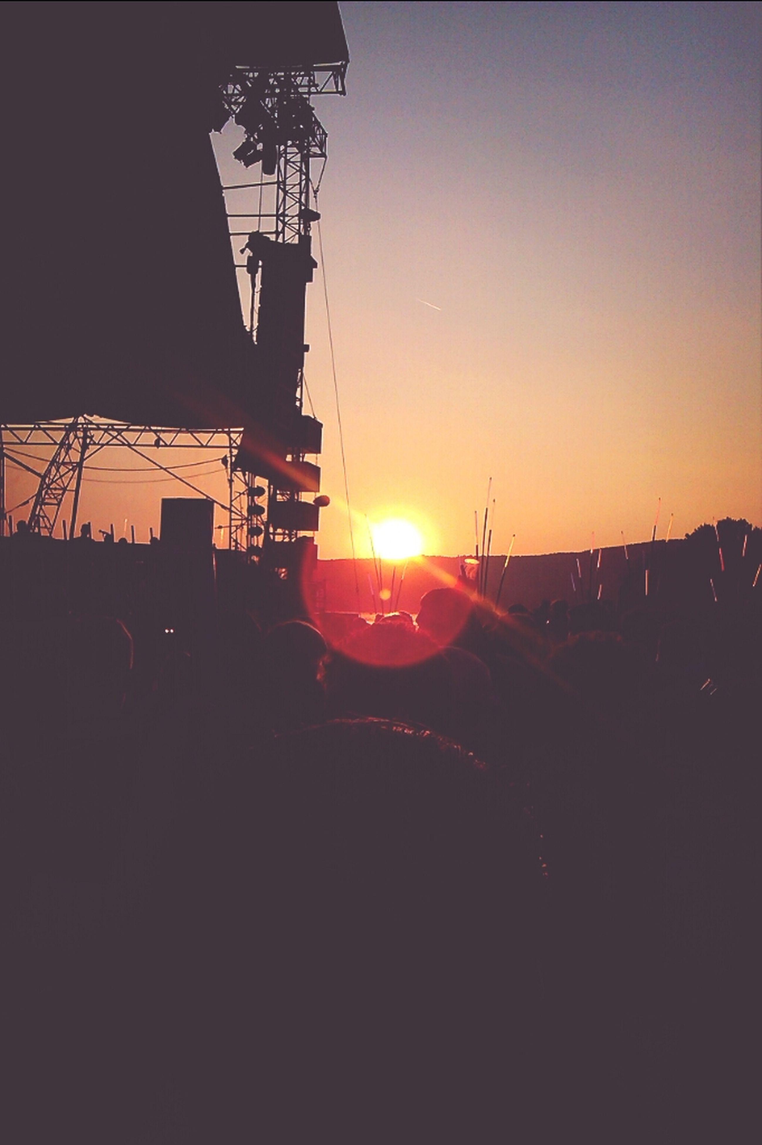sunset, sun, orange color, clear sky, silhouette, sunlight, built structure, sunbeam, copy space, architecture, lens flare, building exterior, transportation, sky, mode of transport, outdoors, nature, construction site, no people, crane - construction machinery