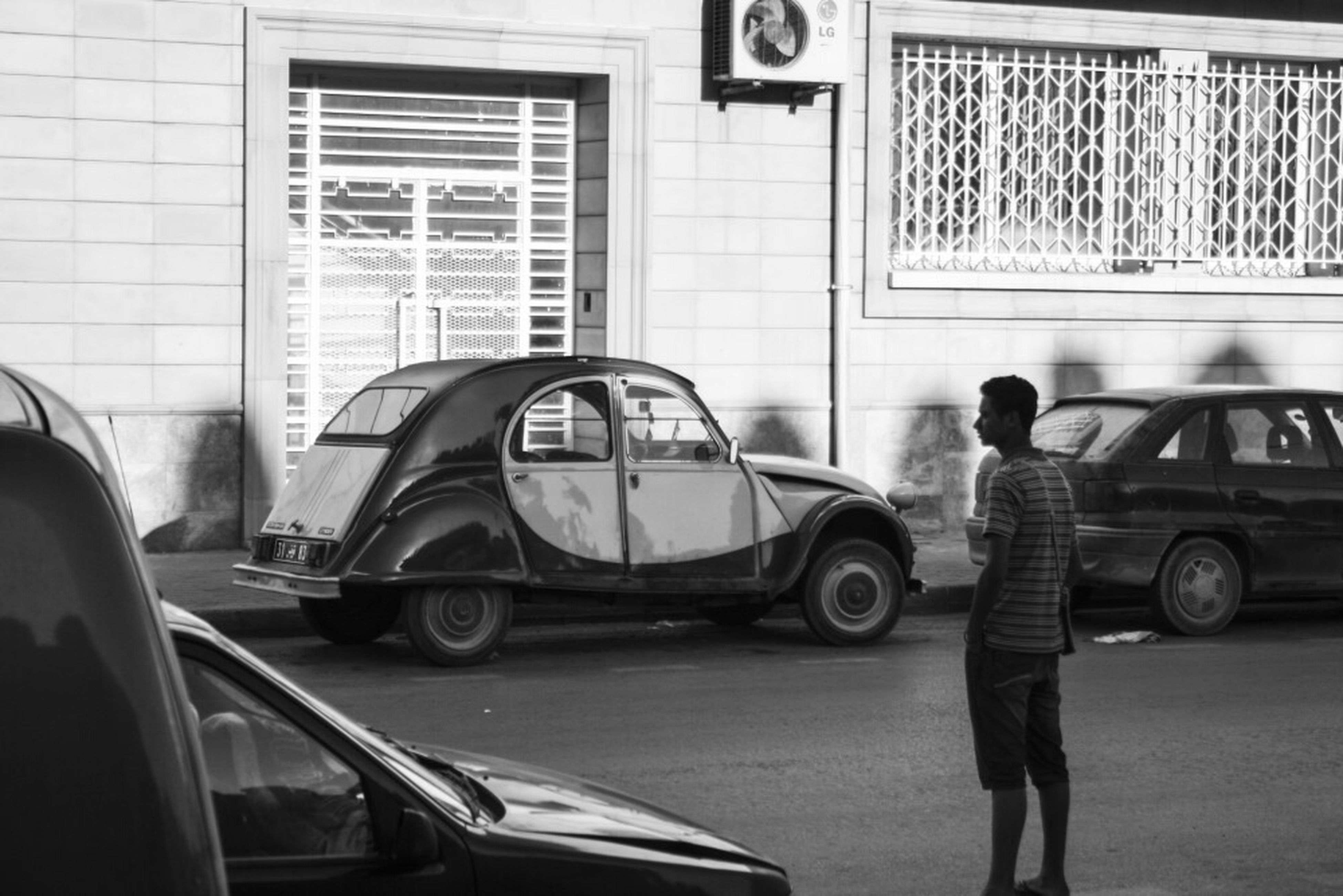 transportation, land vehicle, mode of transport, lifestyles, car, street, building exterior, men, architecture, built structure, rear view, leisure activity, full length, side view, casual clothing, city, window, day