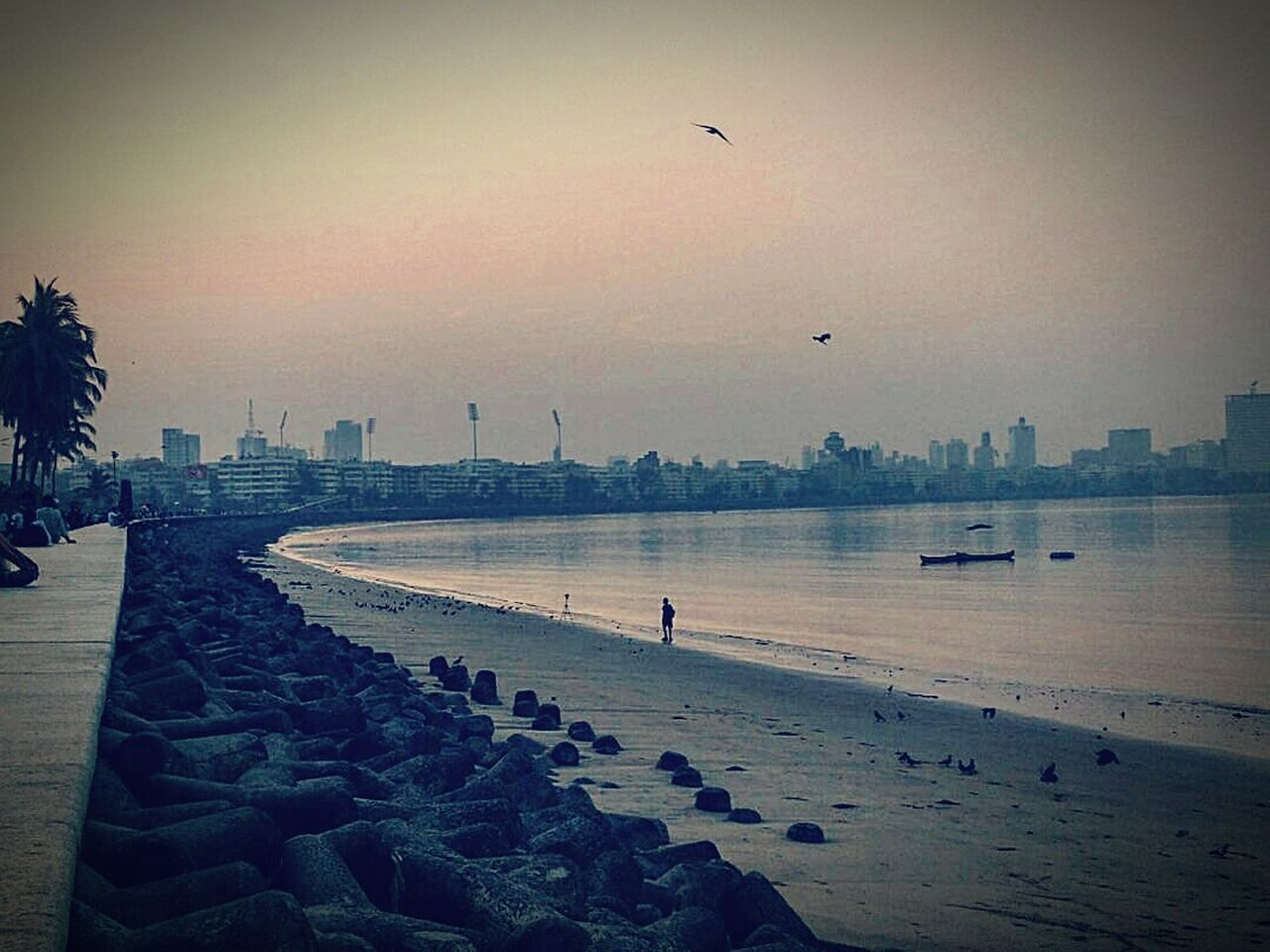 beach, sea, architecture, built structure, real people, water, building exterior, sky, outdoors, sand, sunset, nature, travel destinations, skyscraper, city, beauty in nature, vacations, day, full length, bird, flying, clear sky, scenics, men, one person, people