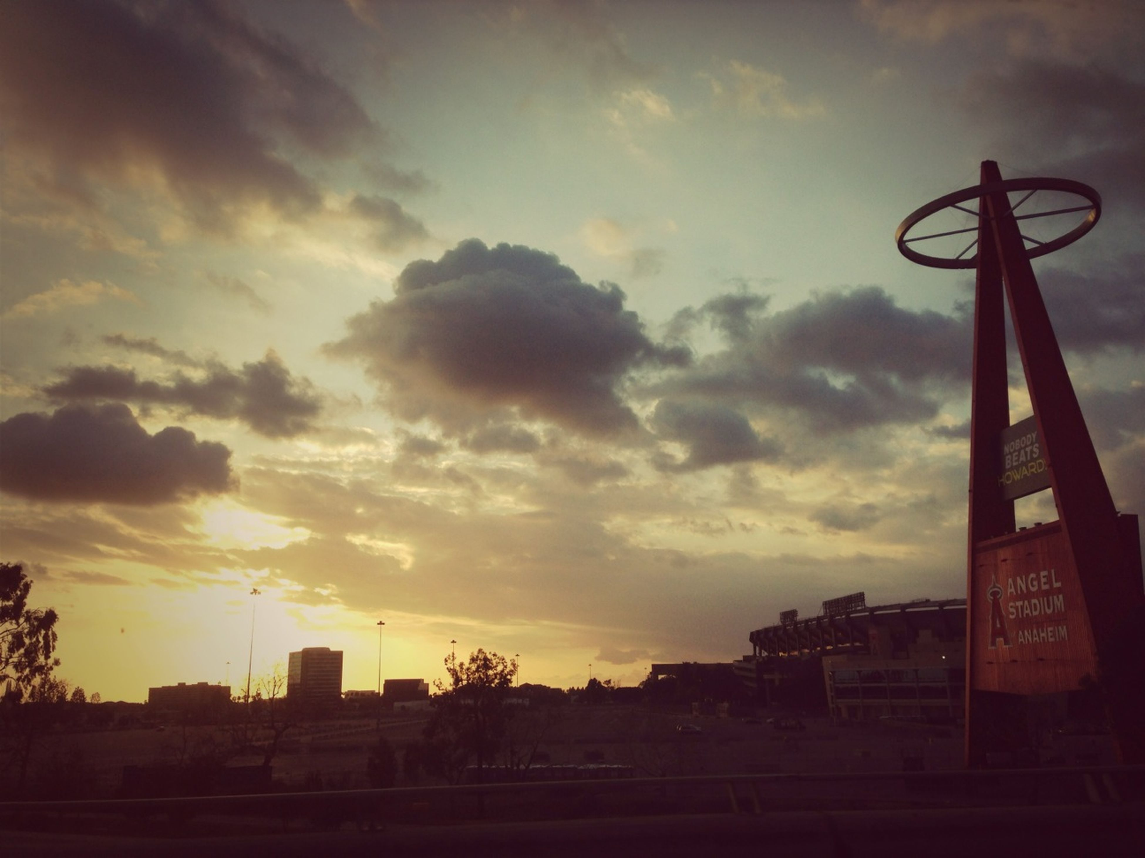 sunset, sky, architecture, built structure, cloud - sky, building exterior, silhouette, low angle view, cloudy, street light, communication, orange color, cloud, city, dusk, outdoors, no people, nature, guidance, dramatic sky
