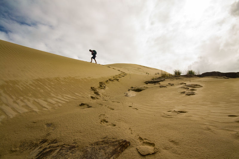 Lost In Dunes. Adventure Arid Climate Beauty In Nature Cloud - Sky Day Desert Full Length Landscape Leisure Activity Lifestyles Men Nature One Person Outdoors People Physical Geography Real People Sand Sand Dune Scenics Sky Small People In Big Places Small Person Small Person Big Story Tranquility