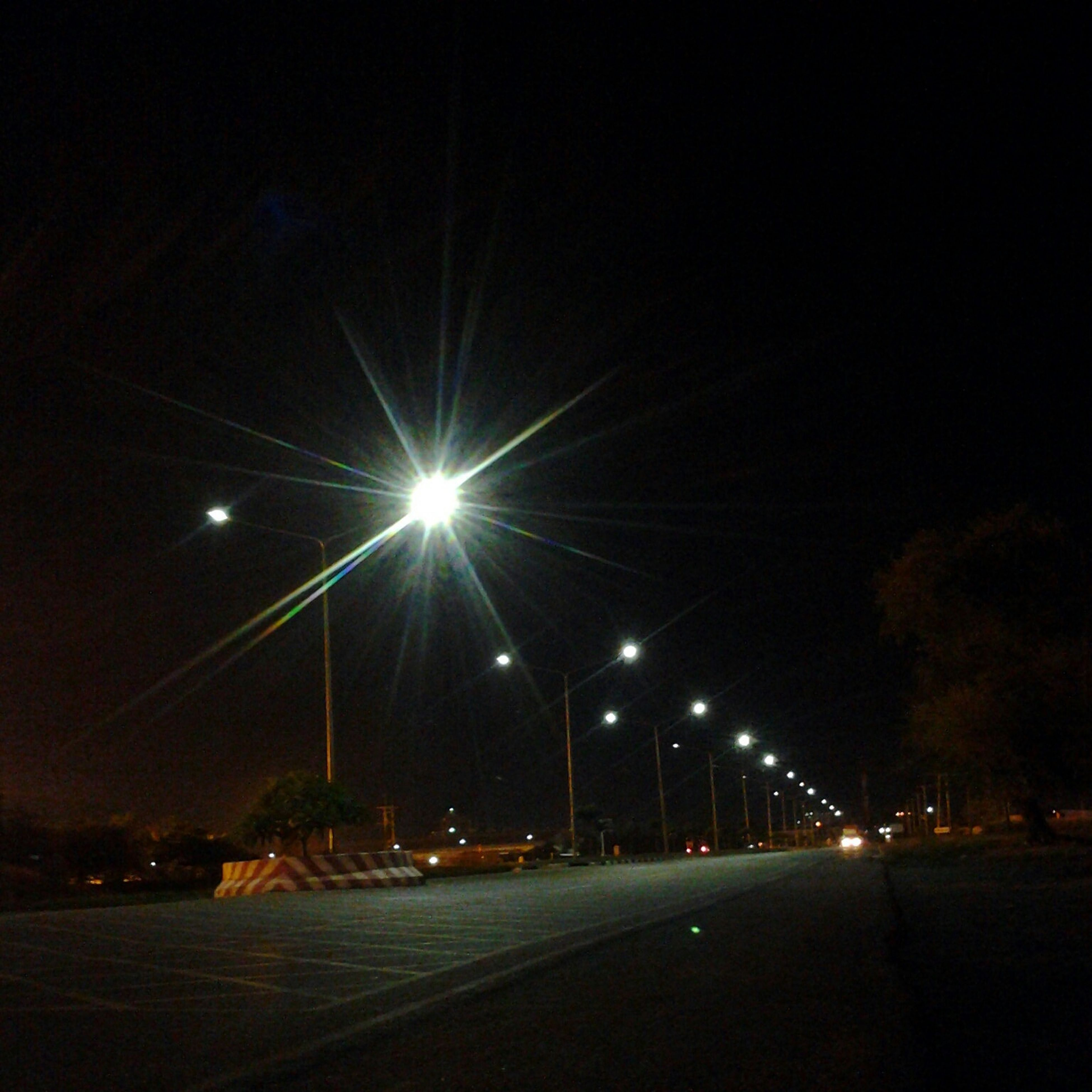night, illuminated, street light, road, transportation, street, the way forward, lighting equipment, car, sky, road marking, copy space, land vehicle, clear sky, outdoors, light - natural phenomenon, dark, diminishing perspective, mode of transport, no people