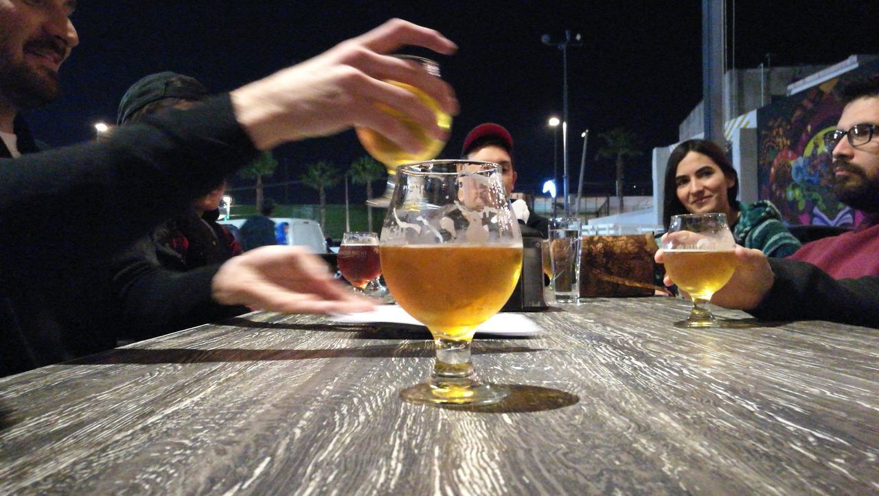 alcohol, food and drink, drink, real people, refreshment, leisure activity, holding, men, lifestyles, indoors, human hand, drinking glass, bar - drink establishment, freshness, happy hour, two people, friendship, human body part, close-up, day, adult, people