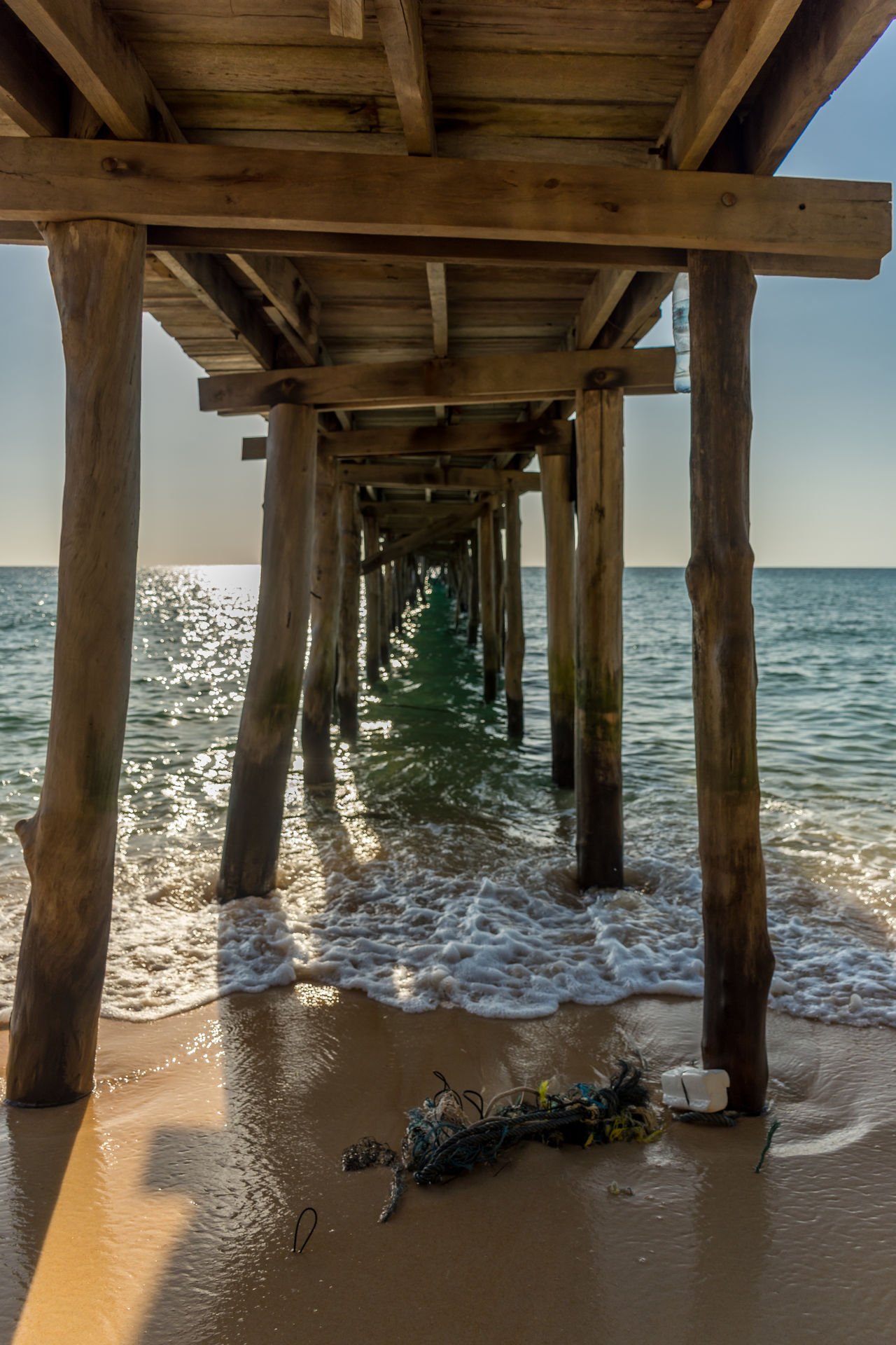View under a old wooden jetty going out to sea from a golden sand beach. Beach Calm Cambodia Golden Horizon Horizon Over Water Island Jetty Ocean Old Outdoors Pier Posts Rubbish Sand Sea Sun Tide Waves Wood Wooden