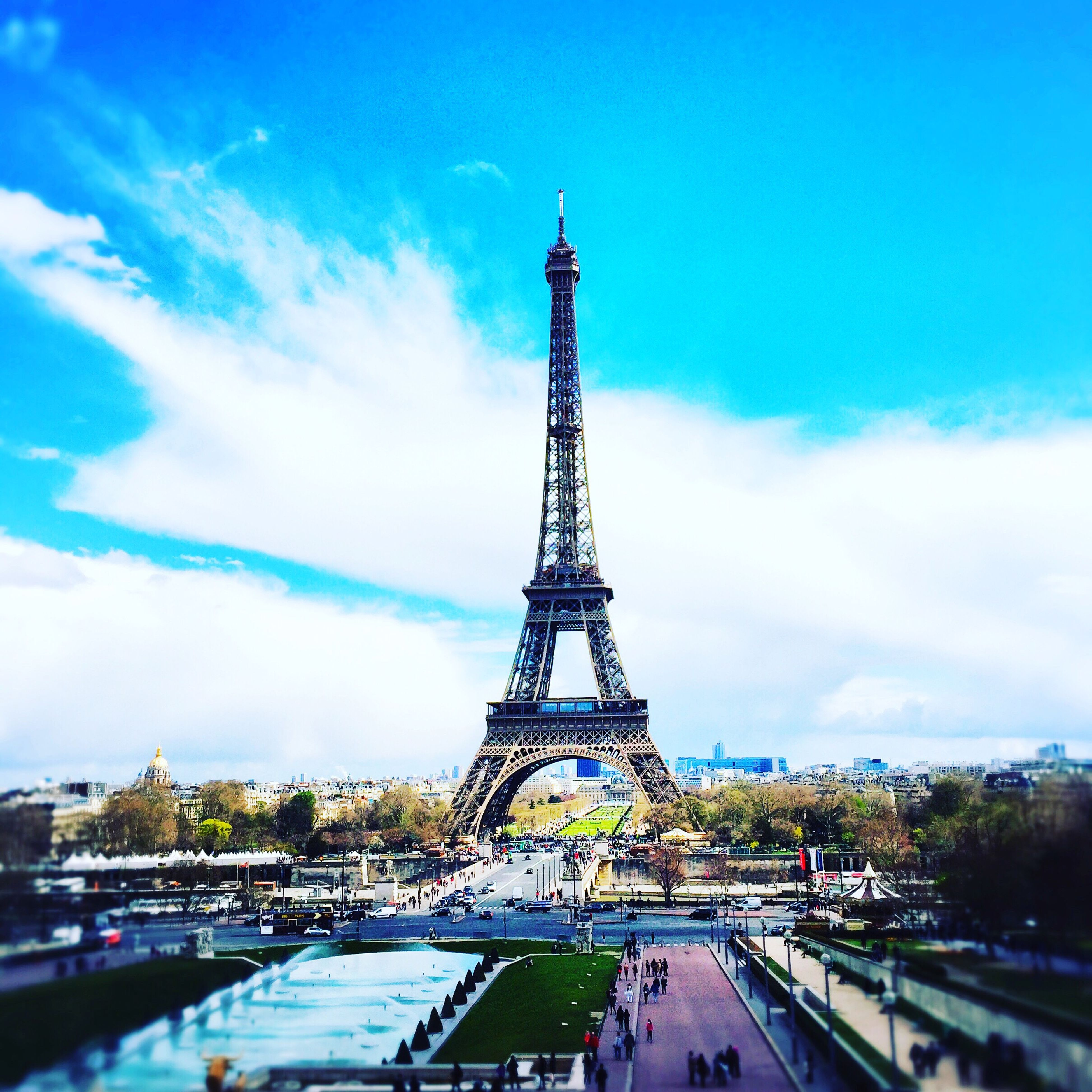 eiffel tower, architecture, built structure, sky, tower, tall - high, cloud - sky, famous place, metal, travel destinations, city, capital cities, building exterior, culture, international landmark, travel, transportation, tourism, road, tree