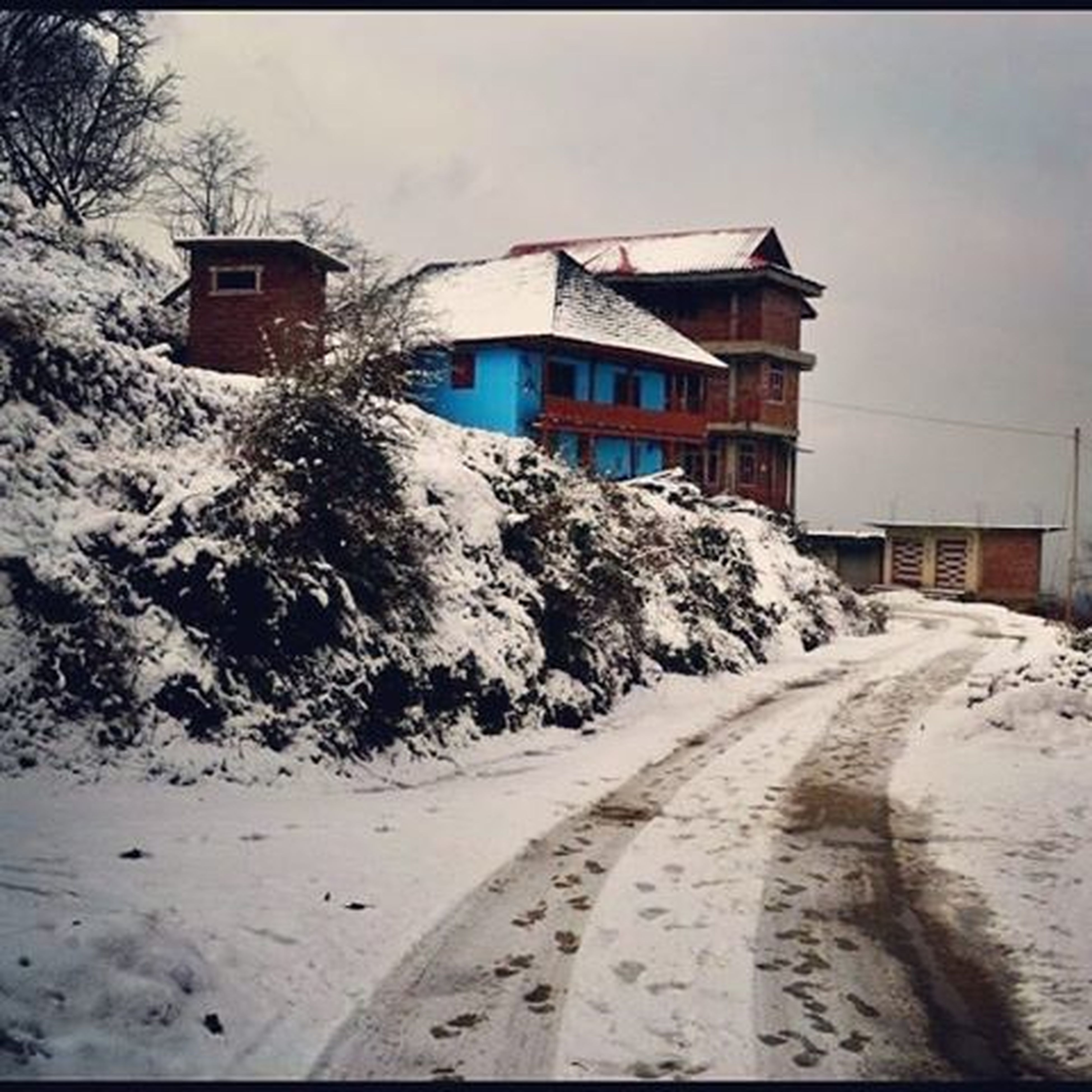 sky, architecture, built structure, building exterior, transportation, road, cloud - sky, snow, house, the way forward, cloud, day, winter, cold temperature, street, outdoors, no people, mountain, nature, weather