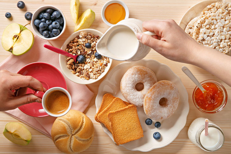 Rich breakfast table. Pouring milk and coffee. Top view Above Apple Berries Bowl Bread Breakfast Cereals Coffee Cup Delicious Donuts Drink Jam Menu Milk Morning Mug Plate Spoon Sweet Table Tasty Toast Top View Variety