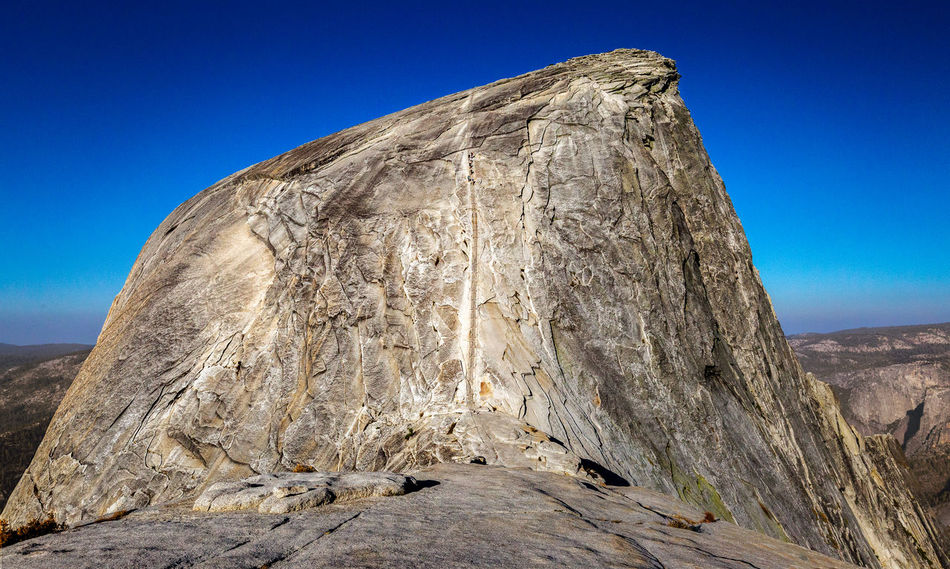 Time to check it off of bucket list   Finally we reached the top of the sub dome. On this fine morning in late-August, the sky was as blue as you can imagine with no clouds whatsoever. And still early enough to see the sun hanging low. We gazed at Half Dome. What a majestic sight! One of the famous hikes in the world. So popular that one must win the lottery to hike it. There are so many tips and tricks as well as warnings involving the ascent and the descent because of its steep incline, especially when severe lightning, thunder, and rainstorms are present. There have been casualties particularly when the granite was wet. Also, the traffic along the cables is a problem since there's only one way to go up and/or down. The later one starts, the longer it'll take to finish it due to constant congestions along the cable. That's why we started early, which many do. And before our ascent, we saw only a group of hikers slowly descending the dome. It was time to check it off of the bucket list. Yosemite National Park, CA Adventure Beauty In Nature Blue Sky Cables Clear Sky Day Hike Forest Granite Granite Rocks Half Dome Hiking Mountain Range Mountains Nature No People Outdoors Permit Scenics Sierra Nevada Sky Sub Dome Sunlight Yosemite National Park Yosemite Point Yosemite Valley