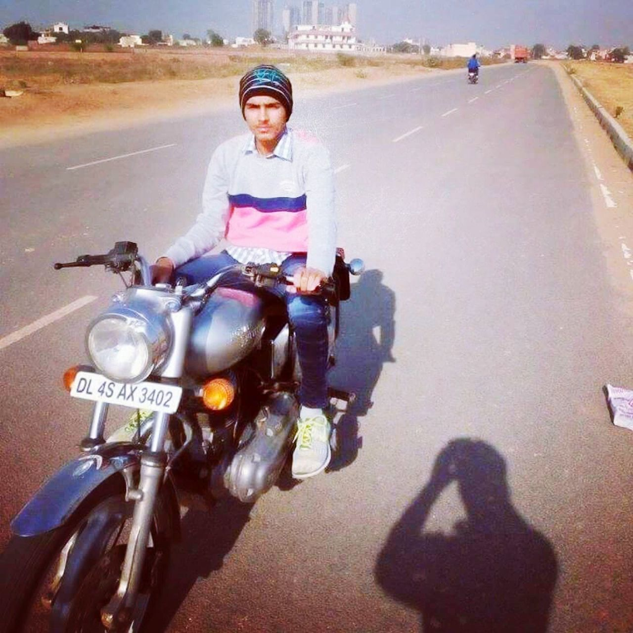 motorcycle, transportation, riding, helmet, portrait, crash helmet, road, looking at camera, land vehicle, mode of transport, front view, lifestyles, shadow, real people, street, headwear, sports helmet, one person, adventure, leisure activity, biker, scooter, sitting, outdoors, day, childhood, people, adult