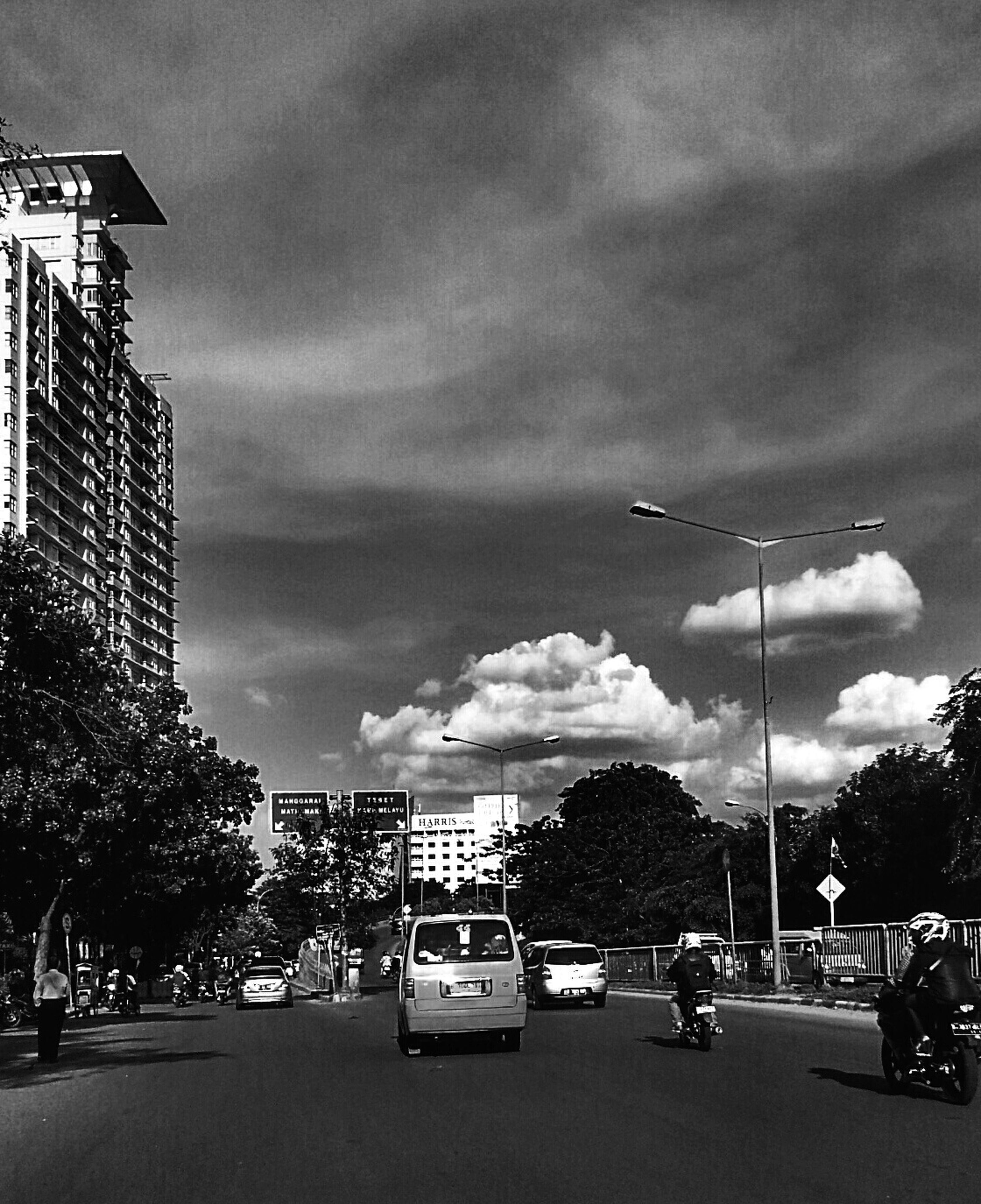 sky, transportation, cloud - sky, building exterior, car, land vehicle, cloudy, mode of transport, built structure, architecture, city, street, street light, road, overcast, cloud, dusk, city life, road marking, city street