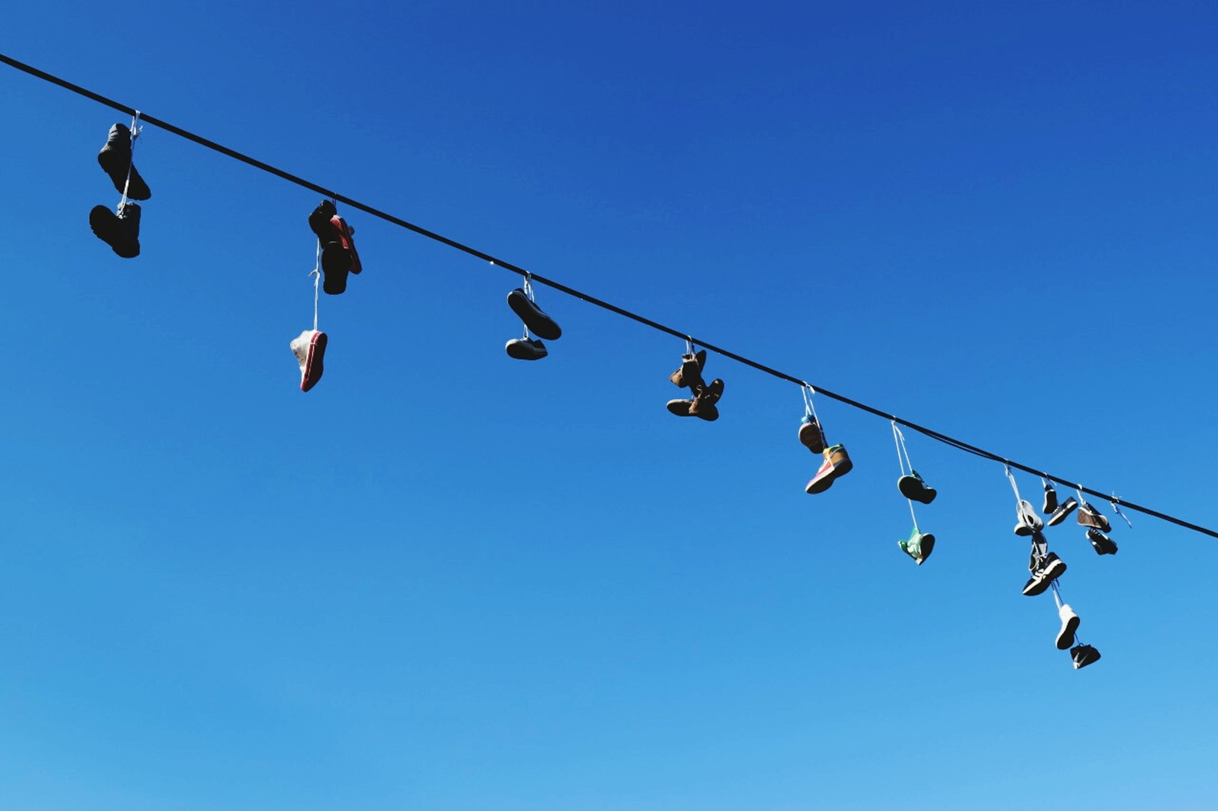 hanging, low angle view, blue, clear sky, cable, in a row, shoe, rope, clothesline, clothespin, day, bizarre, large group of objects, string, group of objects, nature, summer, laundry, power line, medium group of objects, tranquility, multi colored