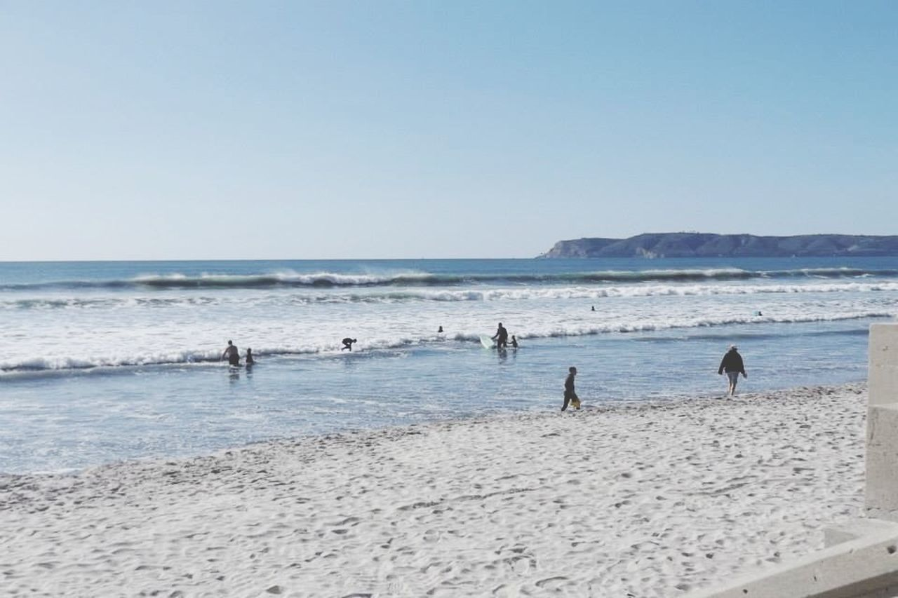 People Enjoying On Beach Against Clear Sky