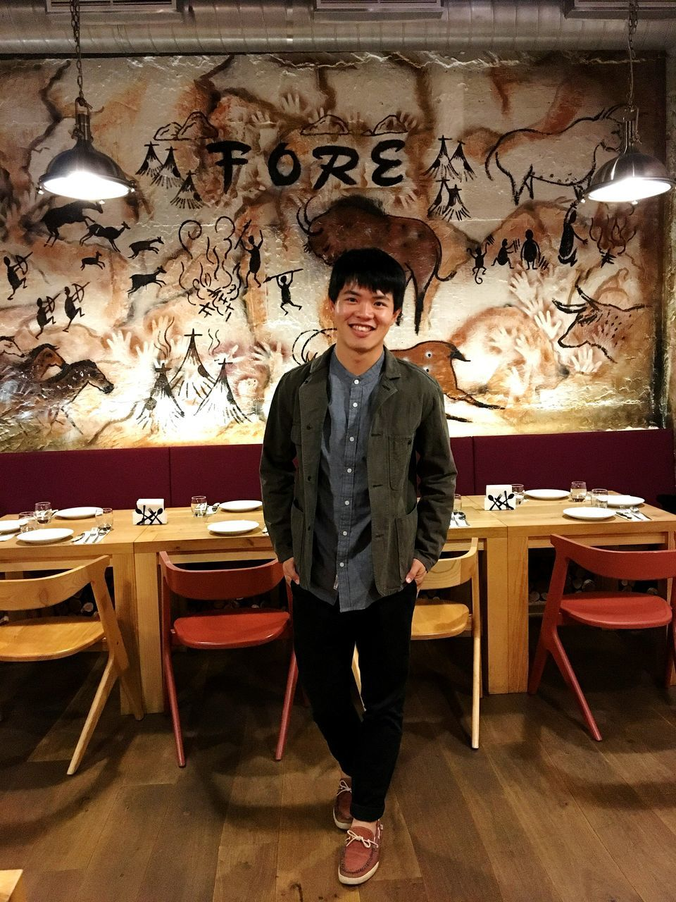 looking at camera, portrait, front view, young adult, one person, full length, standing, restaurant, real people, young men, indoors, table, confidence, casual clothing, lifestyles, smiling, cafe, handsome, day, one young man only, people