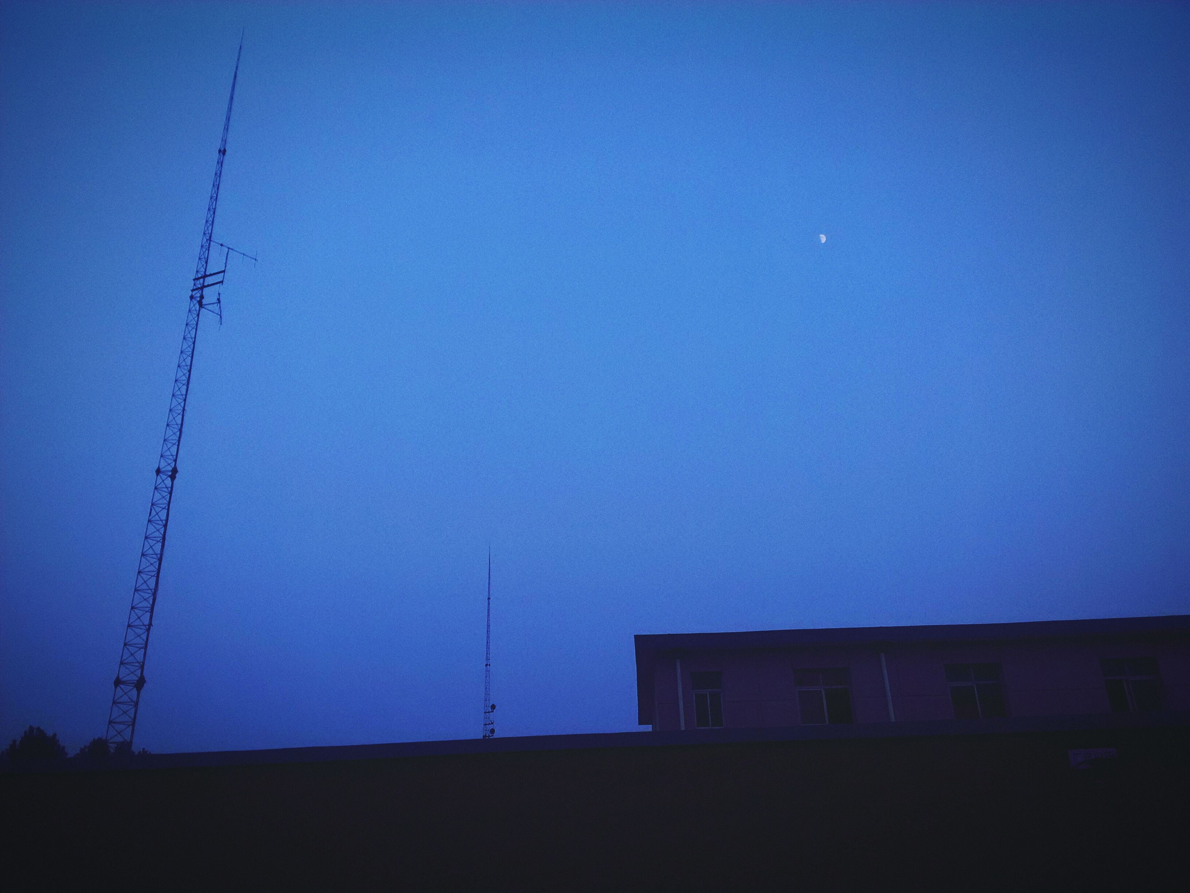 power line, electricity, electricity pylon, low angle view, built structure, clear sky, copy space, power supply, building exterior, architecture, cable, silhouette, blue, connection, fuel and power generation, dusk, technology, sky, house, power cable