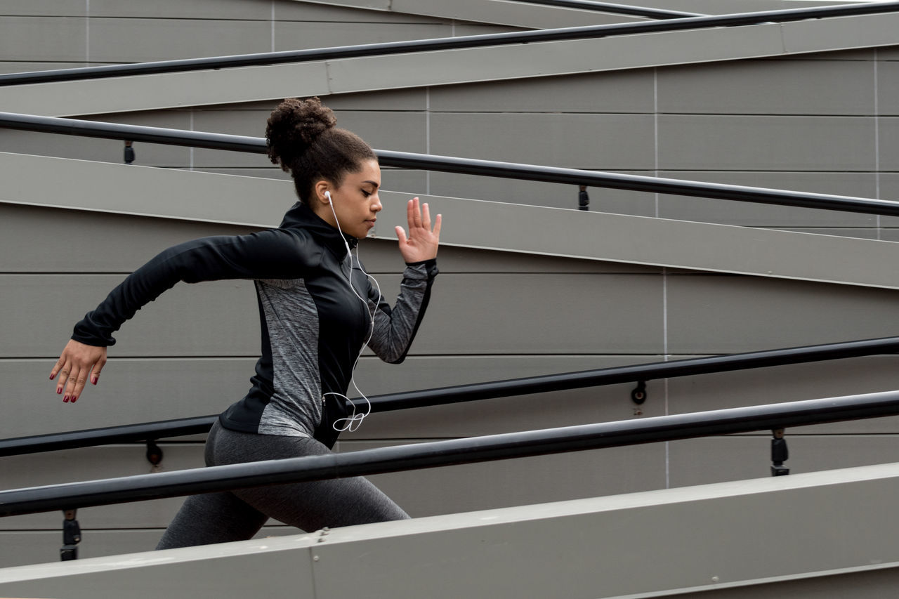 Activity Adult Adults Only Agility Exercising Female Full Length Healthy Lifestyle Jogger One Person One Woman Only Outdoors People Real People Running Sport Sport Clothes Staircase Steps And Staircases Urban Women Young Adult Young Women