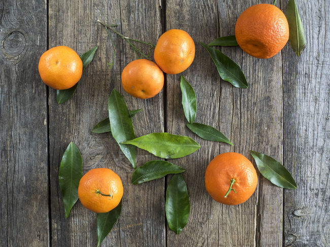 Overhead view of Tangerines with leaves on rustic wooden boards Boards Citrus Fruit Close-up Day Food Freshness Fruit Leaf Leaves No People Overhead Rustic Tangerines View Wood - Material Wooden