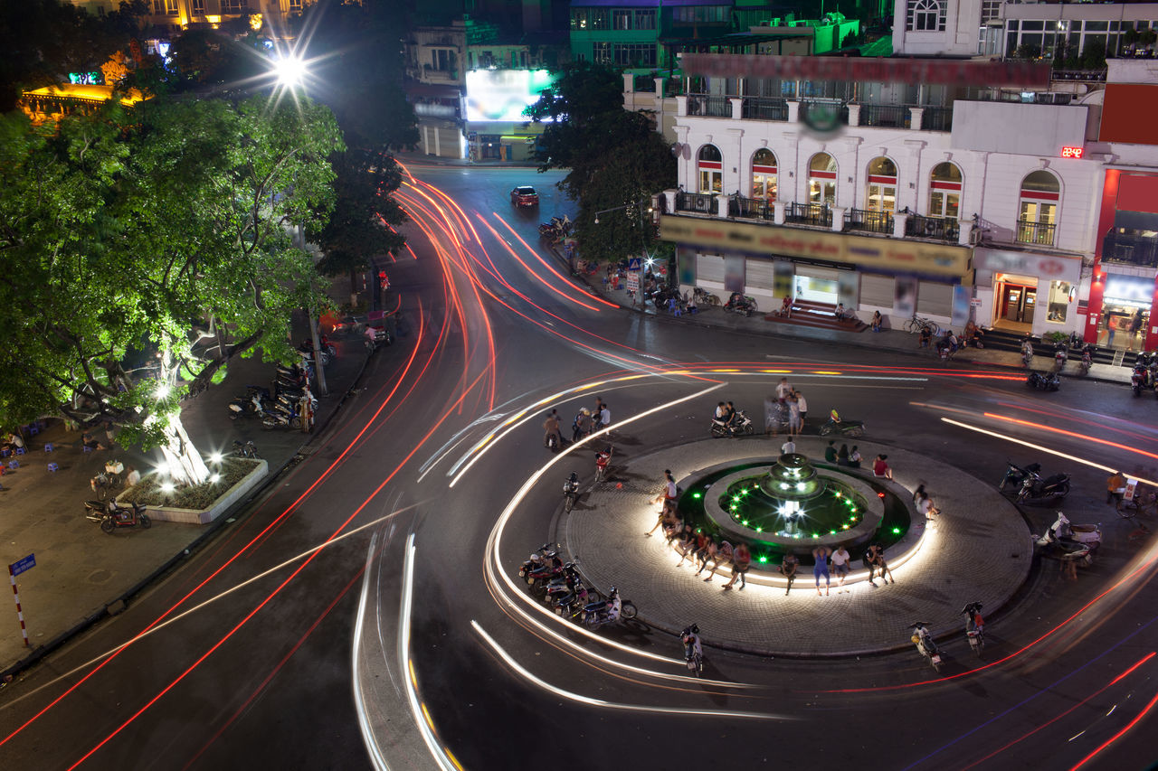 Night view of illuminated fountain on the city square and transport moving around it. White and red traffic trails in motion. Hanoi, Vietnam Architecture ASIA Building Car City City Life City Street Hanoi Horizontal Illuminated Night Outdoors Road Sguare Speed Street Traffic Traffic Trail Transport Vietnam
