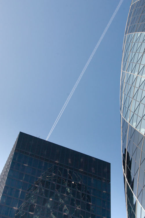 Looking up, London Architecture Buildings Clear Sky Day Glass London Low Angle View Mirrored No People Outdoors Reflections Sky Skyward Sun Vapor Trail Vertical Windows