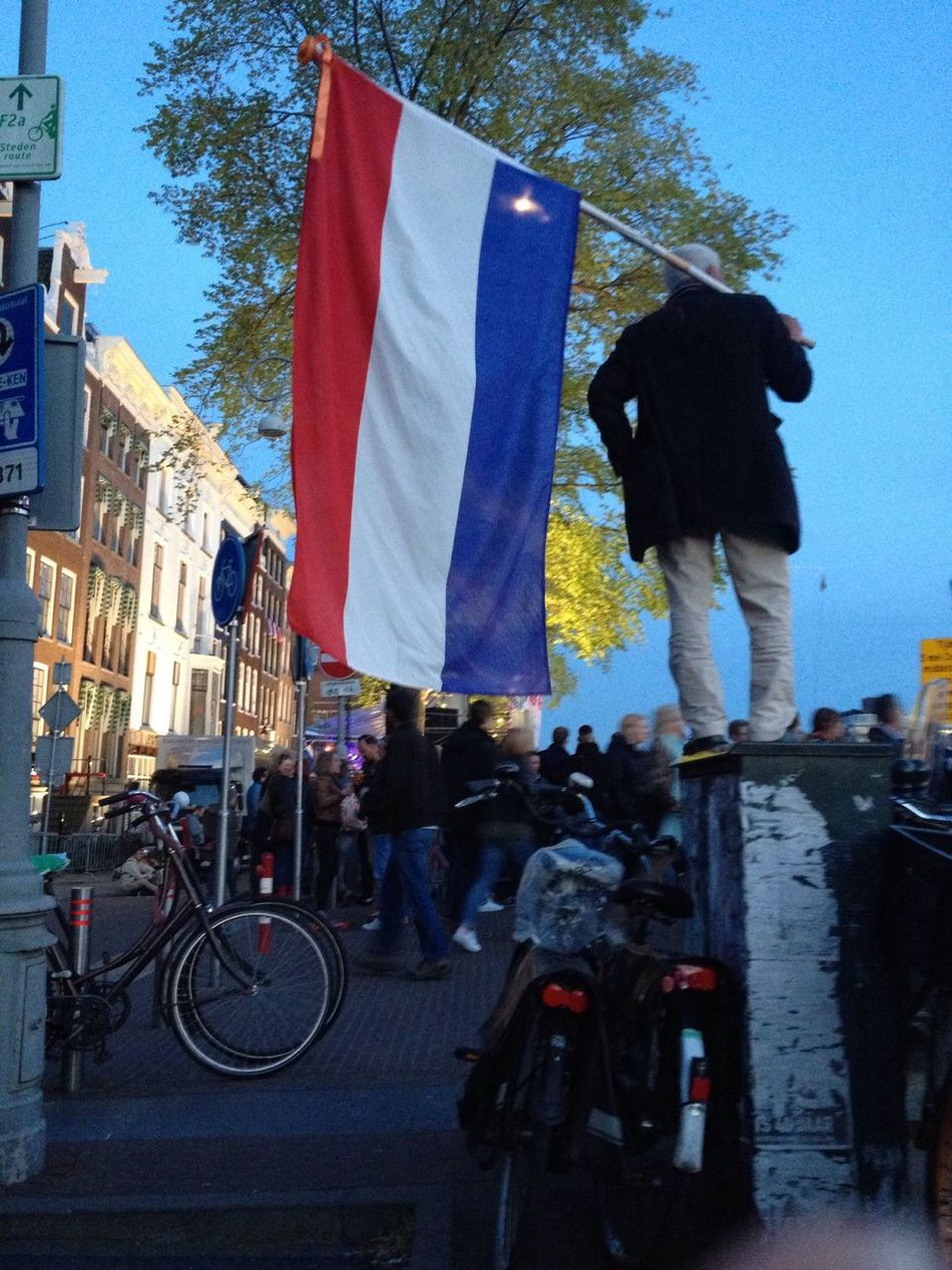 Celebrating Liberationday in Amsterdam Netherlands National Flag Dutch Man Standing Bikes Building Exterior Outside Festivities The Photojournalist - 2016 EyeEm Awards