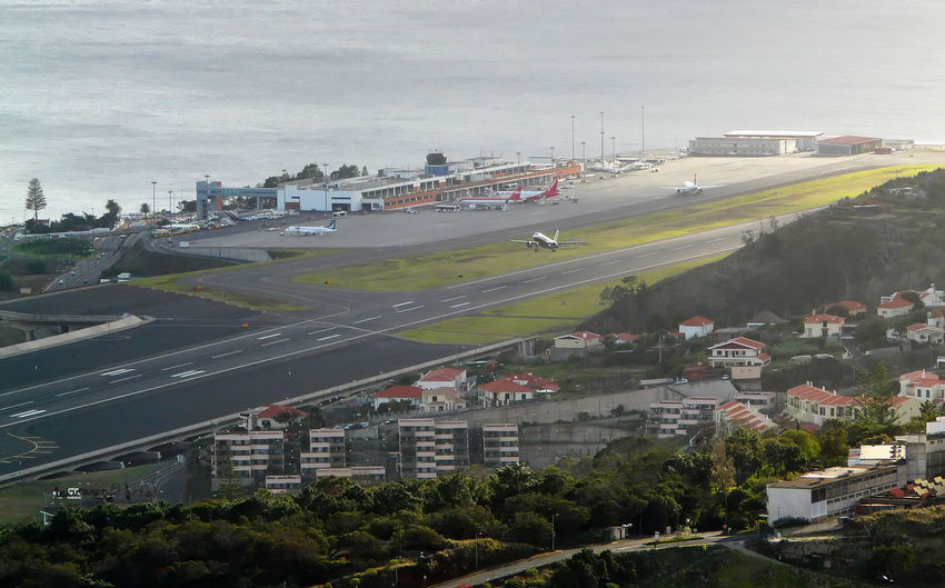 An aircraft takes off from Funchal Airport - Island of Madeira Funchal Airport Madeira Islands, Portugal Take Off Aircraft Taking Off Airplane Airport Airport Runway Architecture Building Exterior Built Structure Car City Cityscape Cloud - Sky Coastal Airport Day High Angle View Madeira Airport Nature No People Outdoors Road Sky Transportation Tree Water