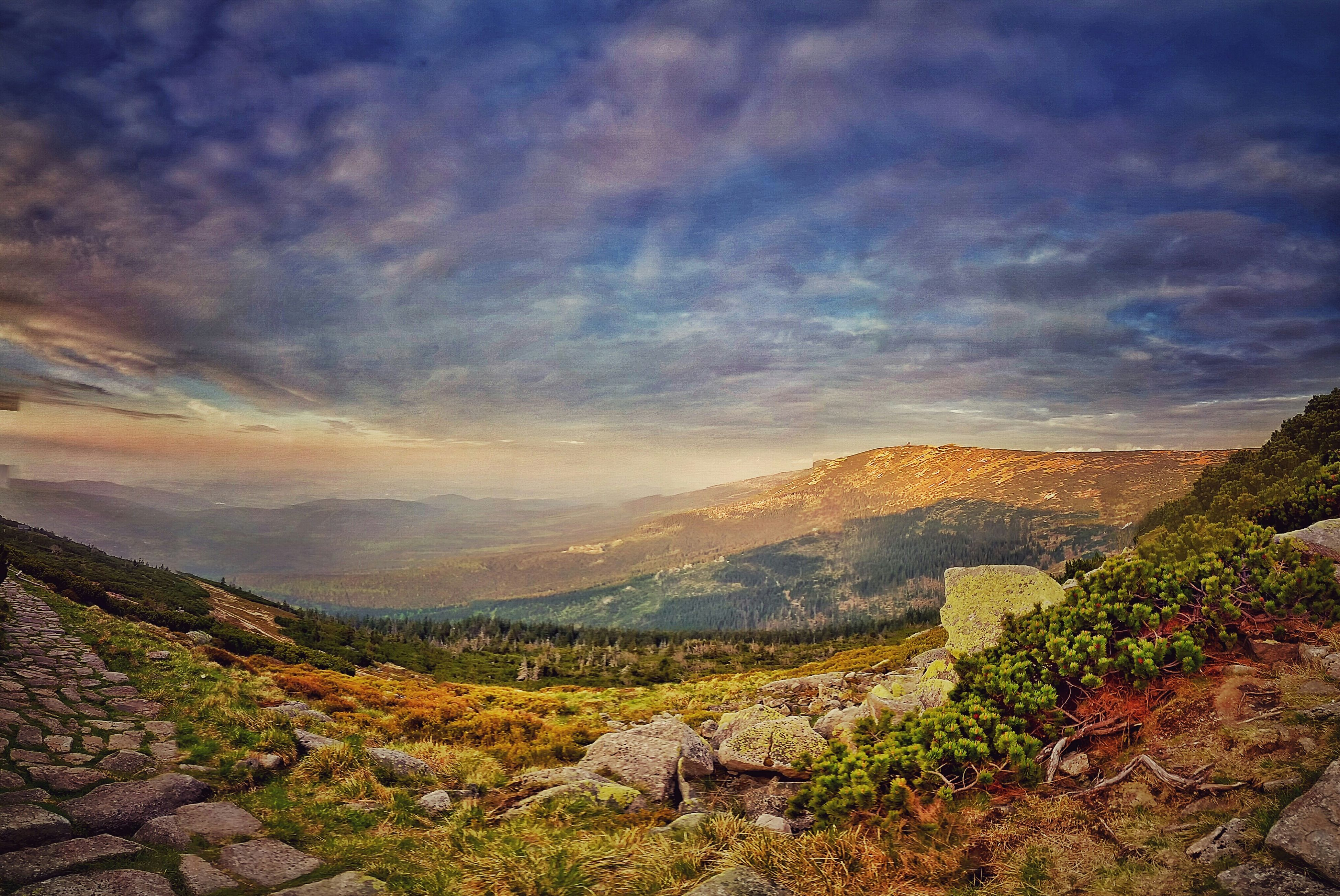 mountain, tranquil scene, sky, tranquility, scenics, landscape, beauty in nature, cloud - sky, mountain range, nature, cloudy, cloud, non-urban scene, idyllic, remote, physical geography, horizon over land, rock - object, rock formation, non urban scene