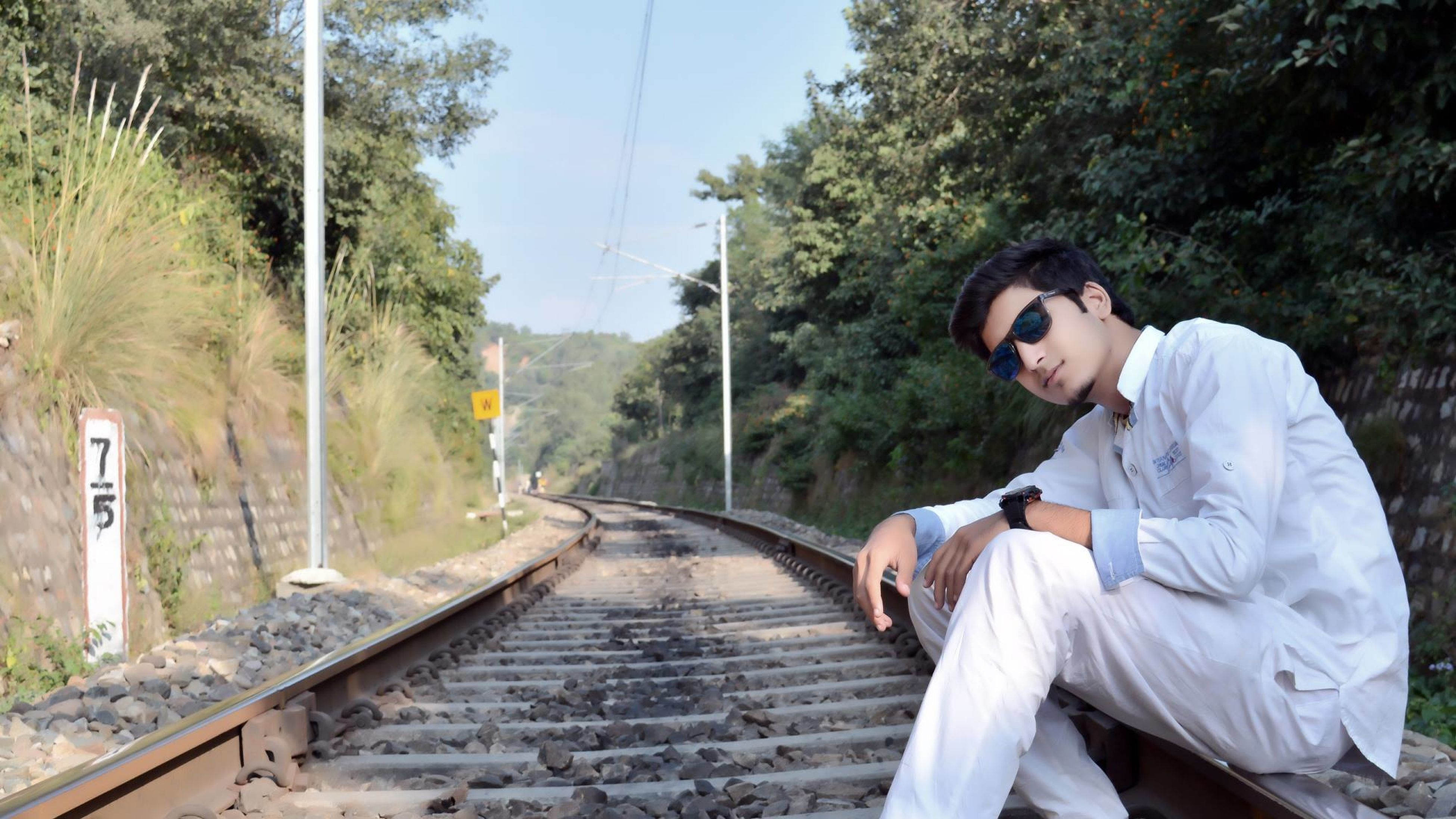 tree, lifestyles, railroad track, young adult, casual clothing, leisure activity, rail transportation, steps, railing, mountain, forest, built structure, day, transportation, the way forward, standing, front view, outdoors