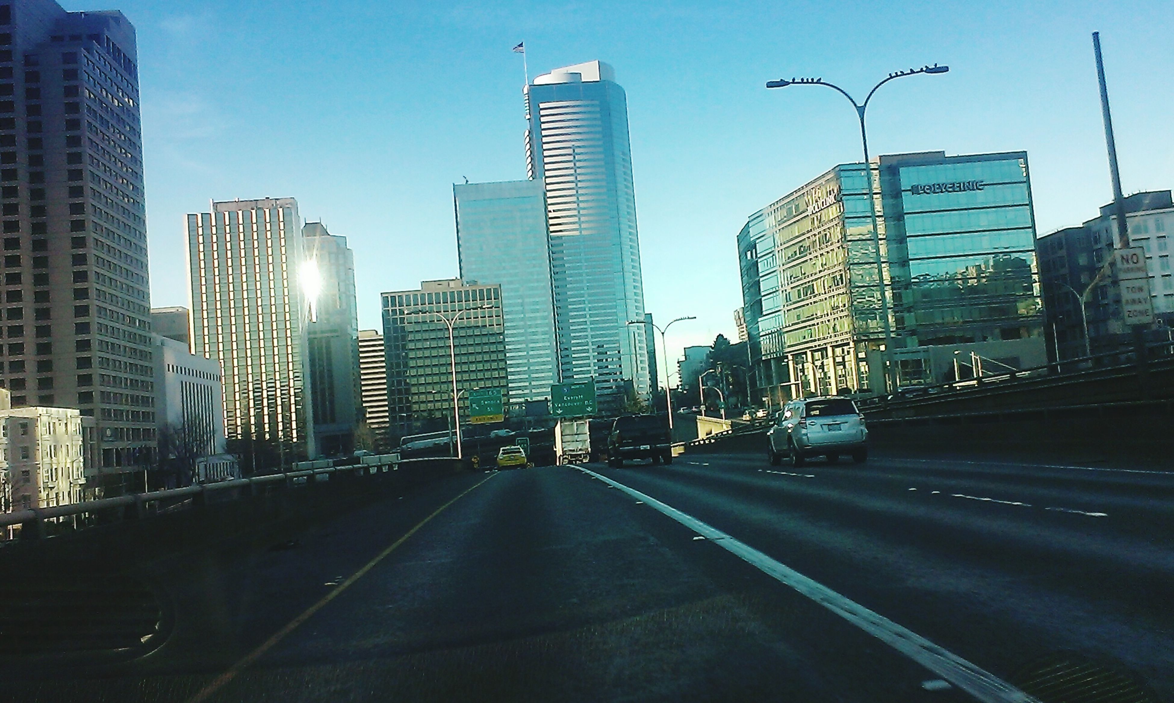 building exterior, architecture, city, built structure, skyscraper, transportation, office building, tall - high, modern, tower, the way forward, road, street, car, building, cityscape, clear sky, city life, financial district, urban skyline
